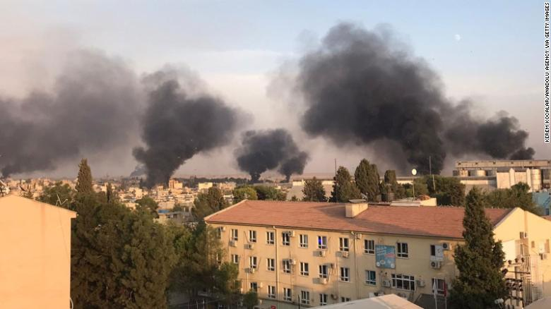 A photo taken from Turkey's Sanliurfa province shows smoke rising over the Syrian town of Ras al-Ayn.