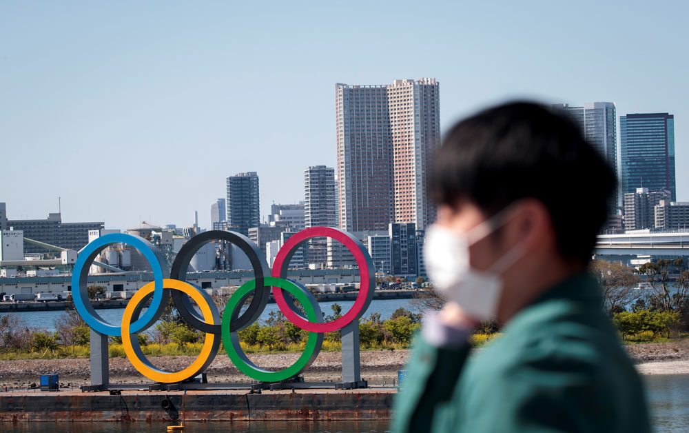 A man wearing a face mask stands before the Olympic rings from an observation point in Tokyo's Odaiba district on March 25.