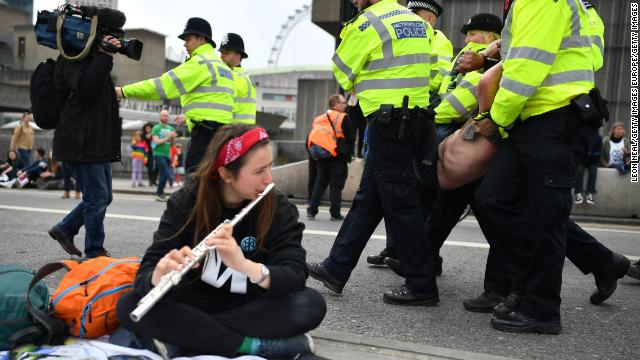 Police officers remove protesters from a blockade on London's Waterloo Bridge during the second day of a coordinated protest by the Extinction Rebellion group on April 16, 2019.
