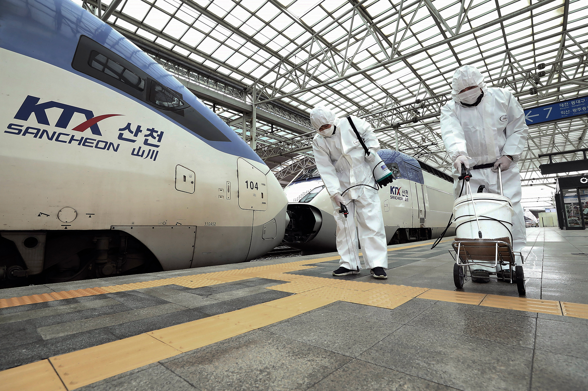 Workers wearing protective gear spray disinfectant as a precaution against the new coronavirus at Seoul Railway Station in Seoul, South Korea, Tuesday, February 25.