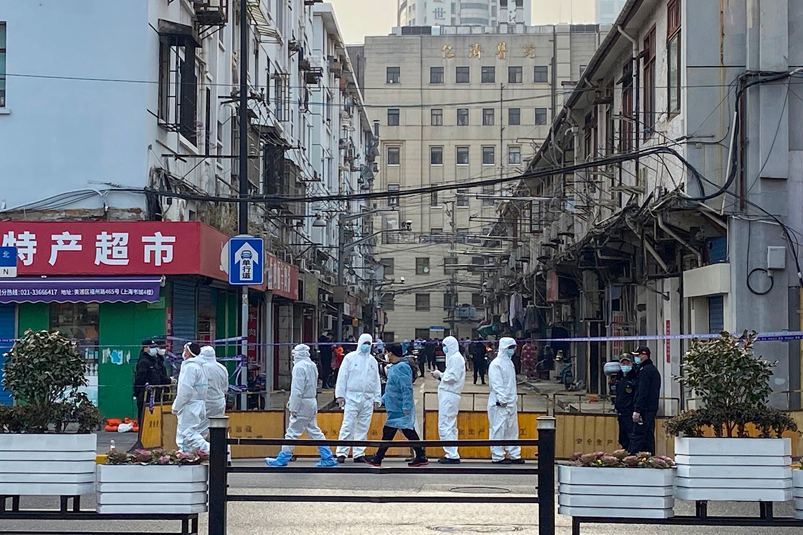 People in protective suits cordon off an area around a residential neighborhood in Shanghai's Huangpu district in China, on January 21.
