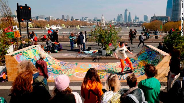 A protester skates on a half-pipe decorated with the Extinction Rebellion logo.