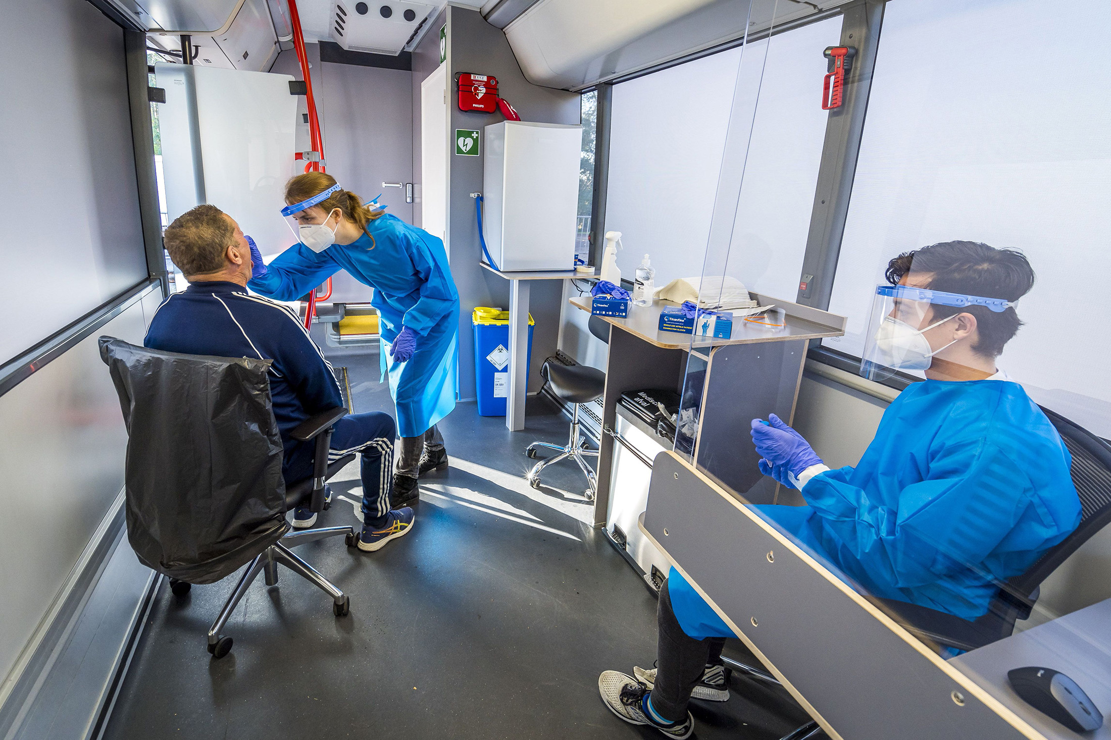 A health worker conducts a swab test on a bus converted into a mobile Covid-19 (coronavirus) test lab, in Hillegom, the Netherlands, on November 9.