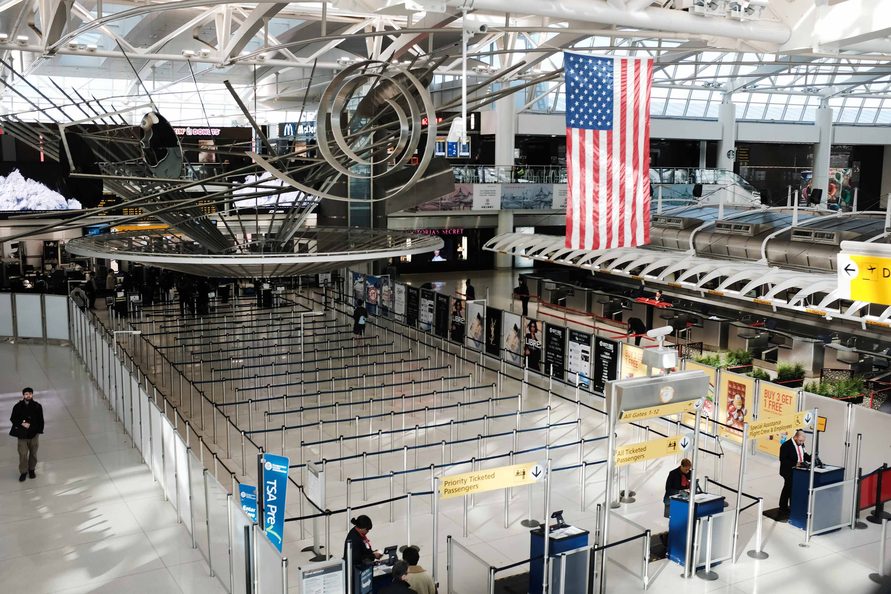 People walk through an international departure terminal at John F. Kennedy Airport in New York City, on March 7.