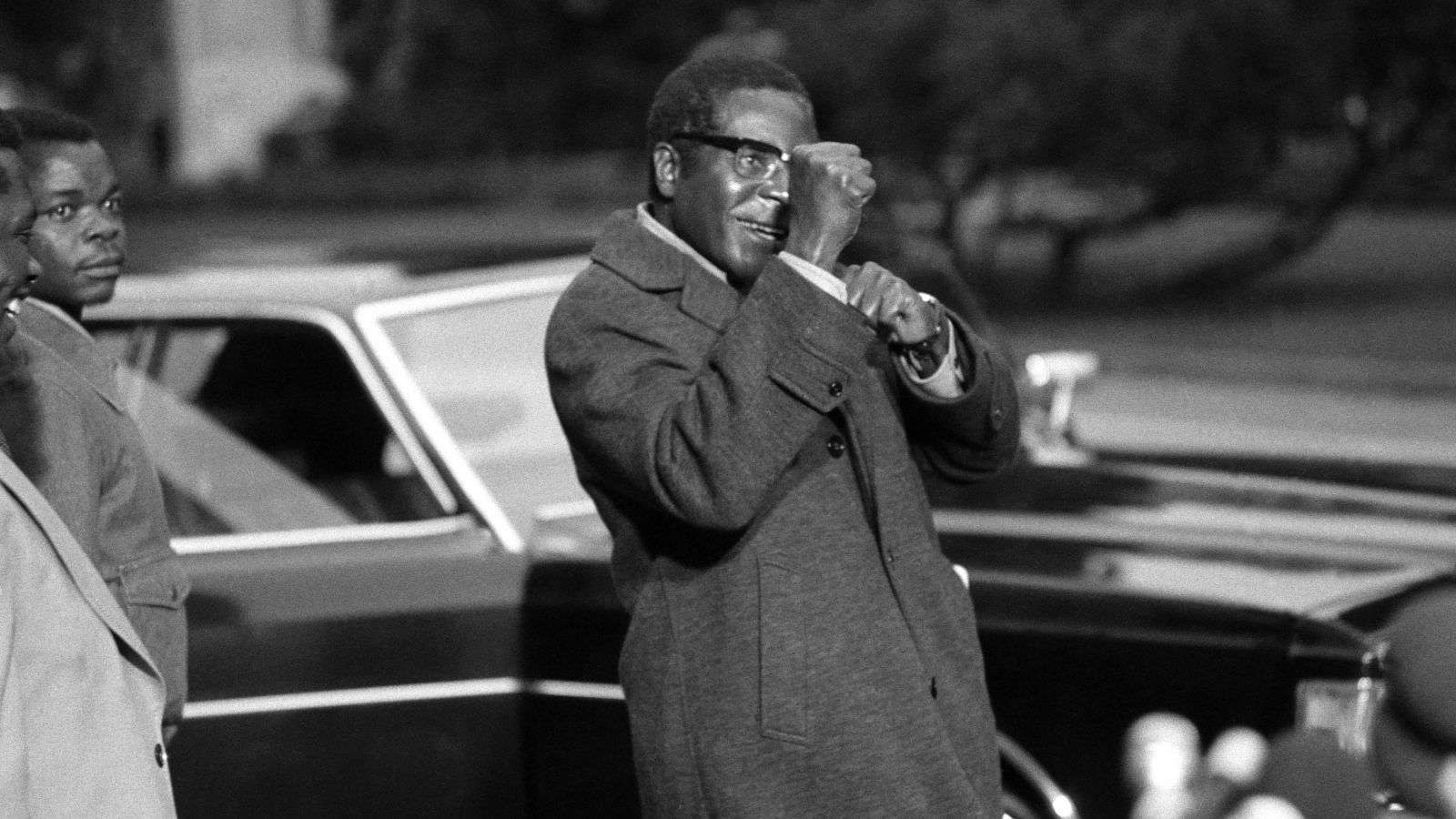 Mugabe gestures towards the media at a Geneva conference convened to address the civil war in Rhodesia. After being imprisoned for 10 years, Mugabe attended the peace talks as a leader of the guerrilla movement ZANU-PF (Zimbabwe African National Union-Patriotic Front). Rhodesia was the state that eventually became Zimbabwe.