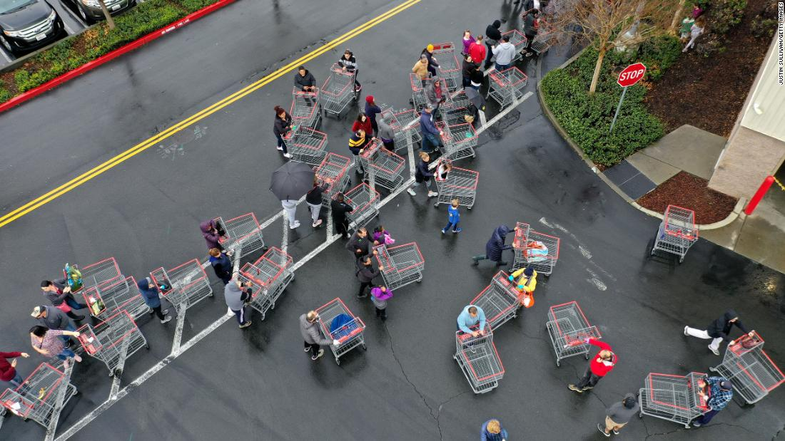 Hundreds of people line up to enter a Costco store on March 14, 2020, in Novato, California.