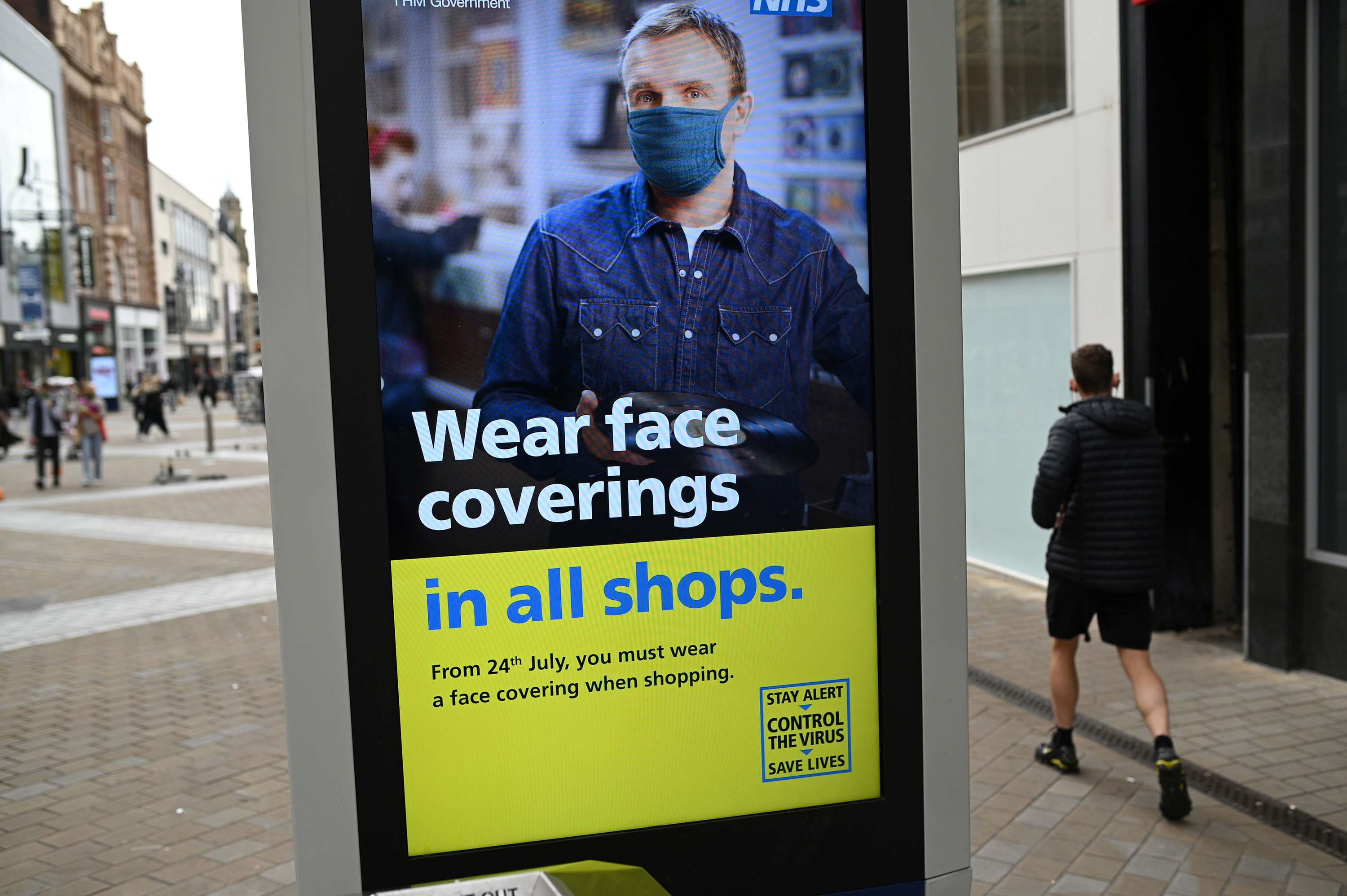 A sign calling for the wearing of face coverings in shops is displayed in Leeds, England, on July 23.