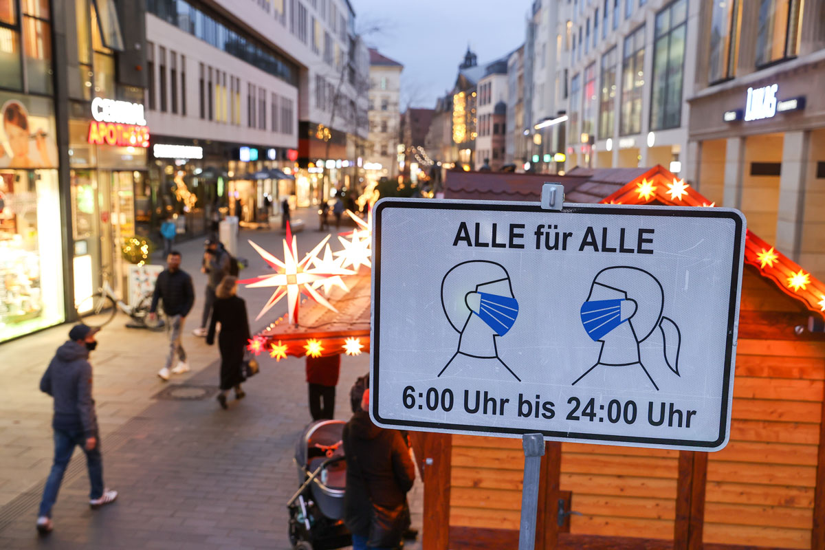 Pedestrians walk past a sign that says mask-wearing is compulsory in Leipzig, Germany amid the coronavirus pandemic on Monday Dec. 7.
