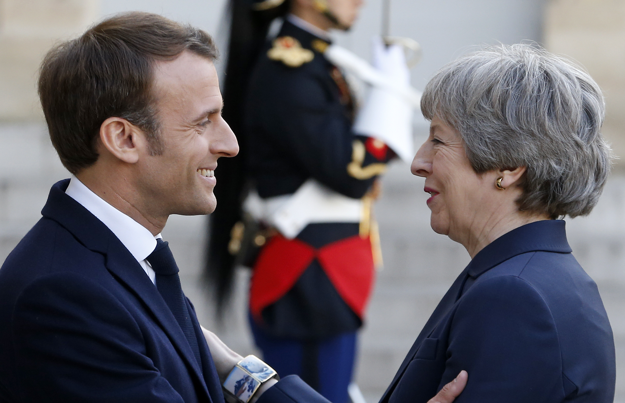 Macron and May greet each other in Paris on Tuesday.