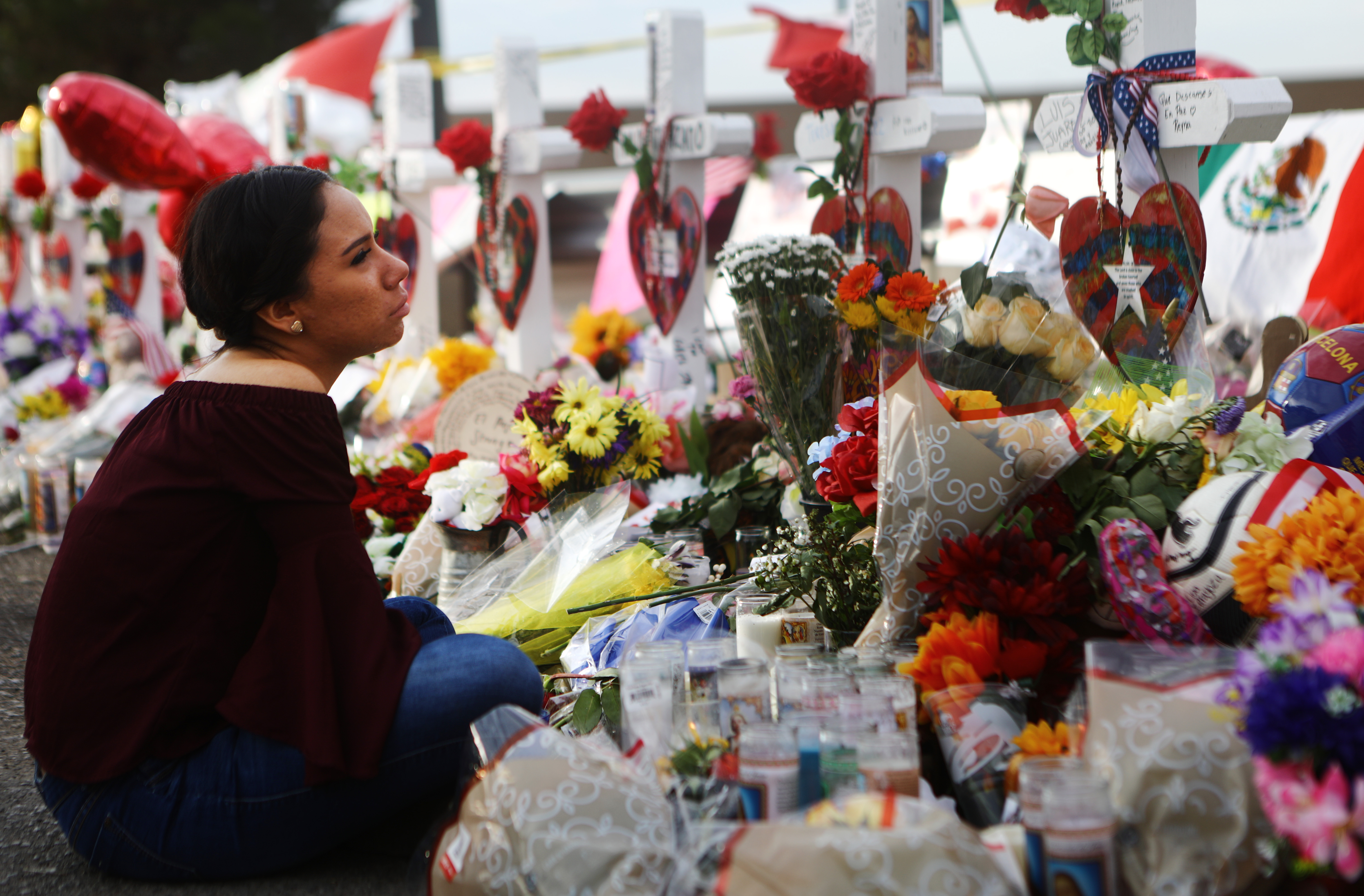 Yamileth Lopez sits while holding a photo of her deceased friend Javier Amir Rodriguez at a makeshift memorial for victims outside Walmart on Aug. 6, 2019 in El Paso, Texas.