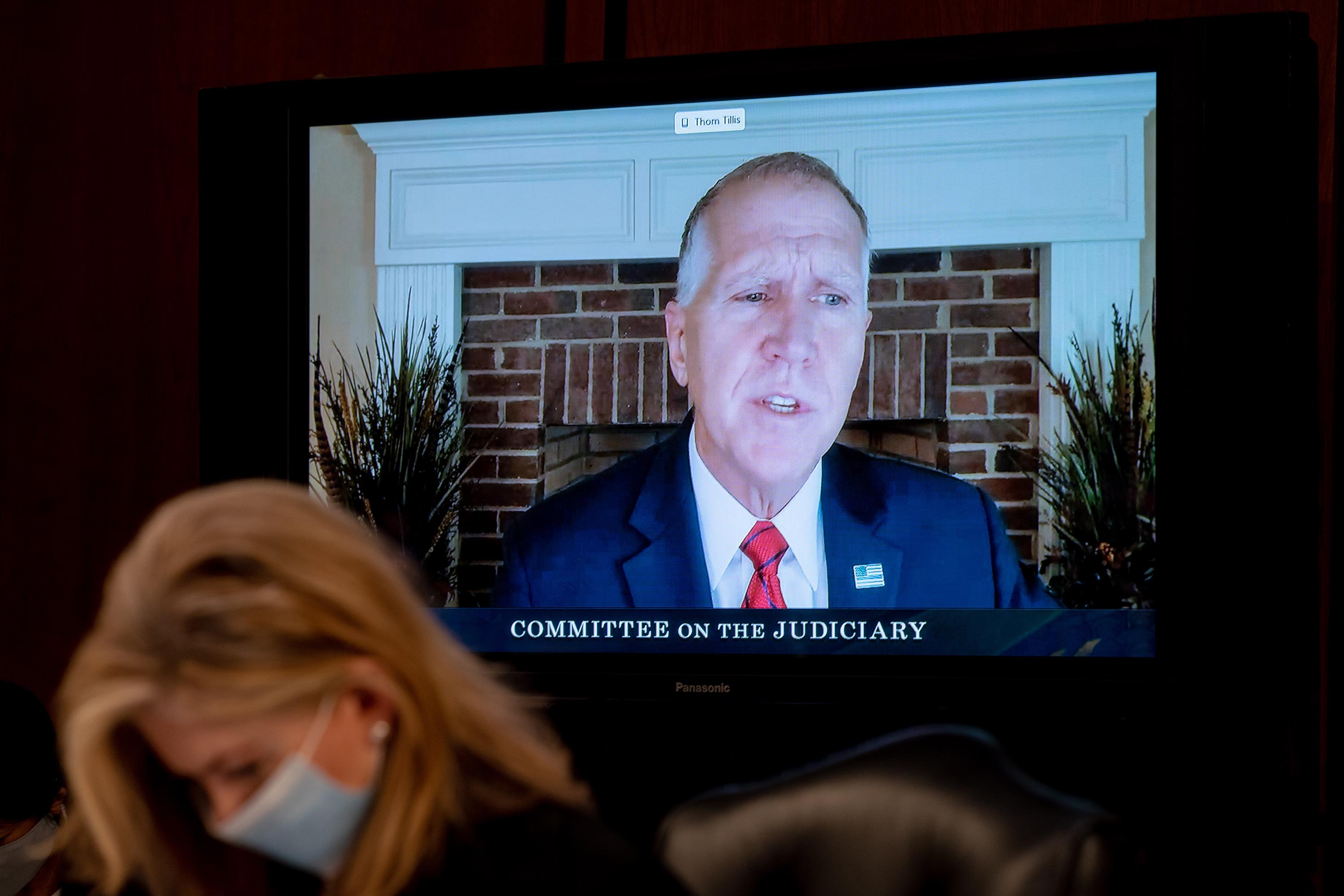 Sen. Thom Tillis is seen on a TV participating remotely during Supreme Court Justice nominee Judge Amy Coney Barrett's Senate Judiciary Committee confirmation hearing on October 12.
