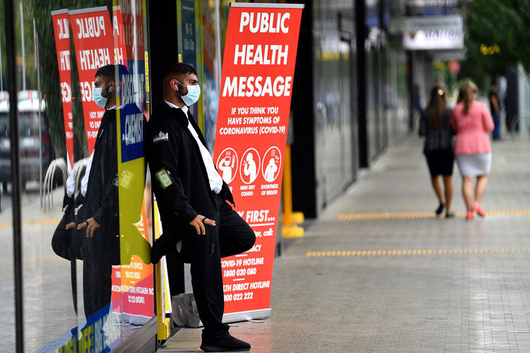 A security guard with a face mask stands outside a pharmacy in Sydney on March 27.