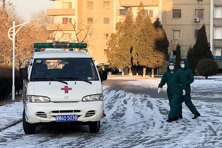 Doctors in medical masks and protective suits by an ambulance vehicle at the Munsu-dong diplomatic compound in Pyongyang, North Korea, amid an outbreak of the coronavirus on February 6.