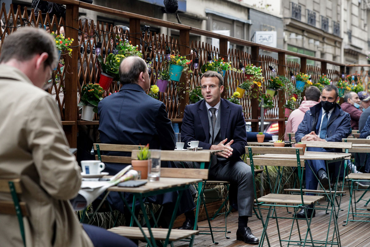 French President Emmanuel Macron (R) and French Prime Minister Jean Castex (L) are having coffees at a cafe terrace in Paris, France on May 19.