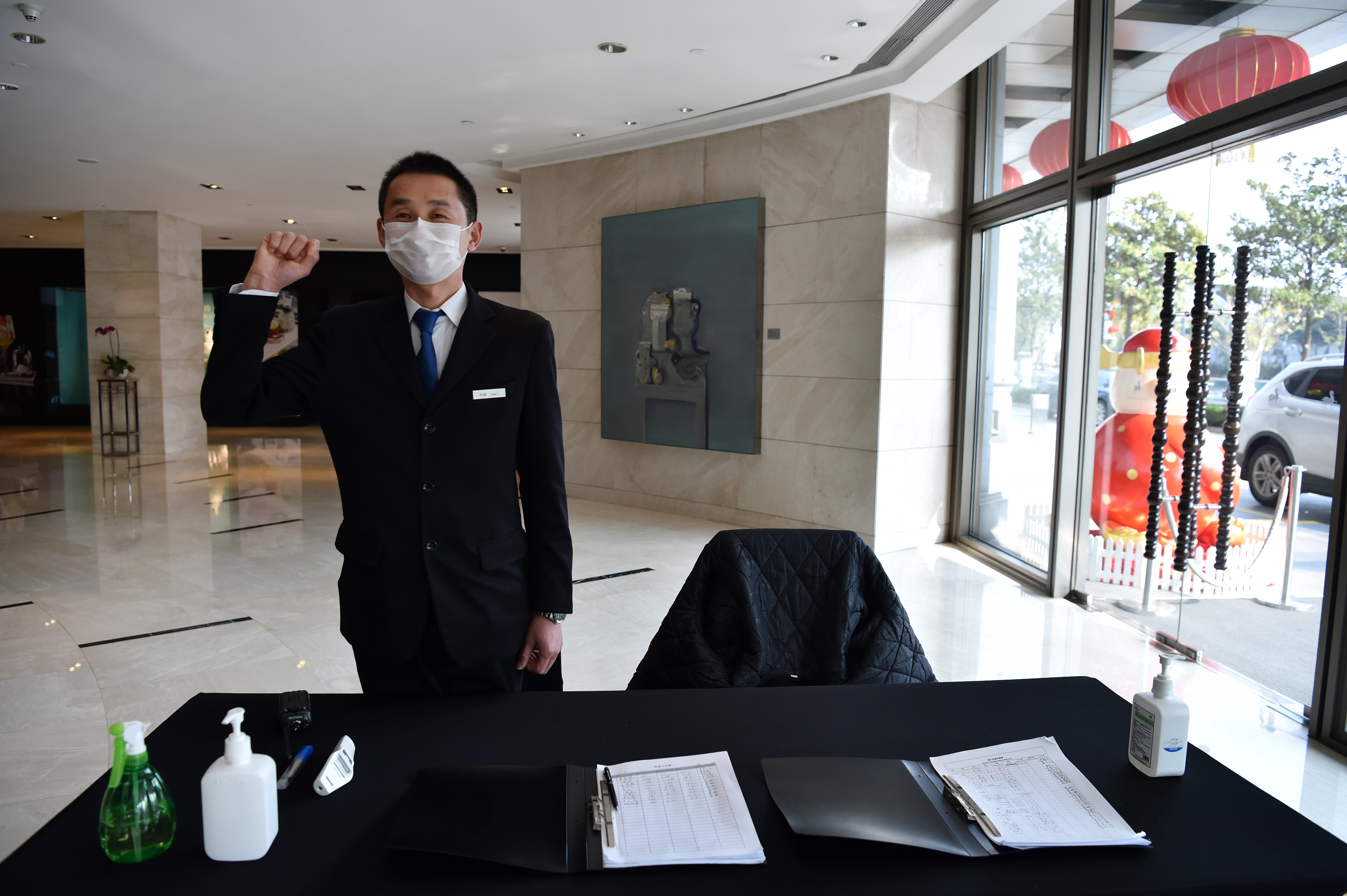 A Wuhan hotel employee ready to take the temperature of anyone who enters the building on January 29, 2020.