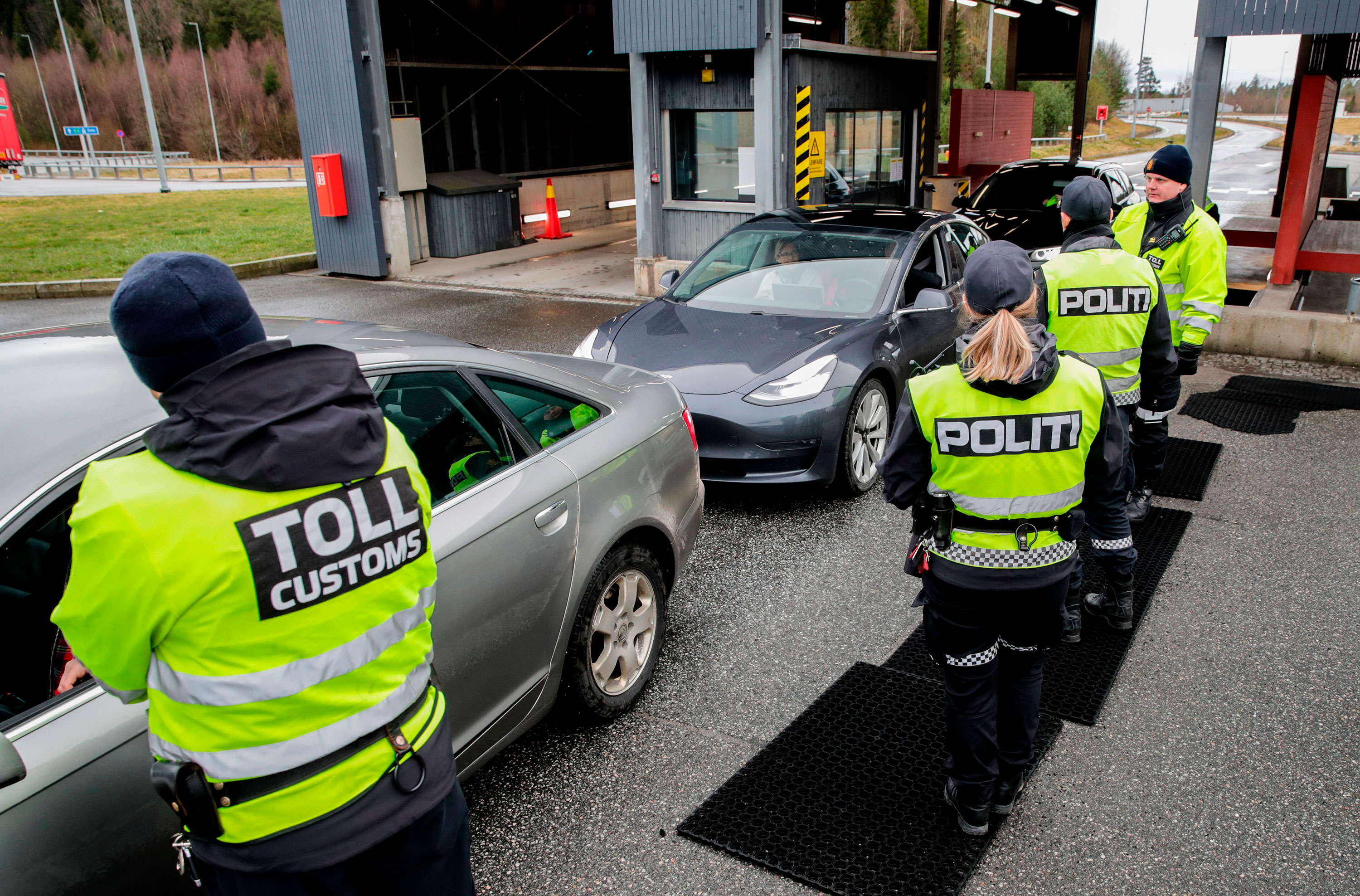 Customs officers and policemen check drivers at the border between Norway and Sweden in Swinesund on March 16, 2020.