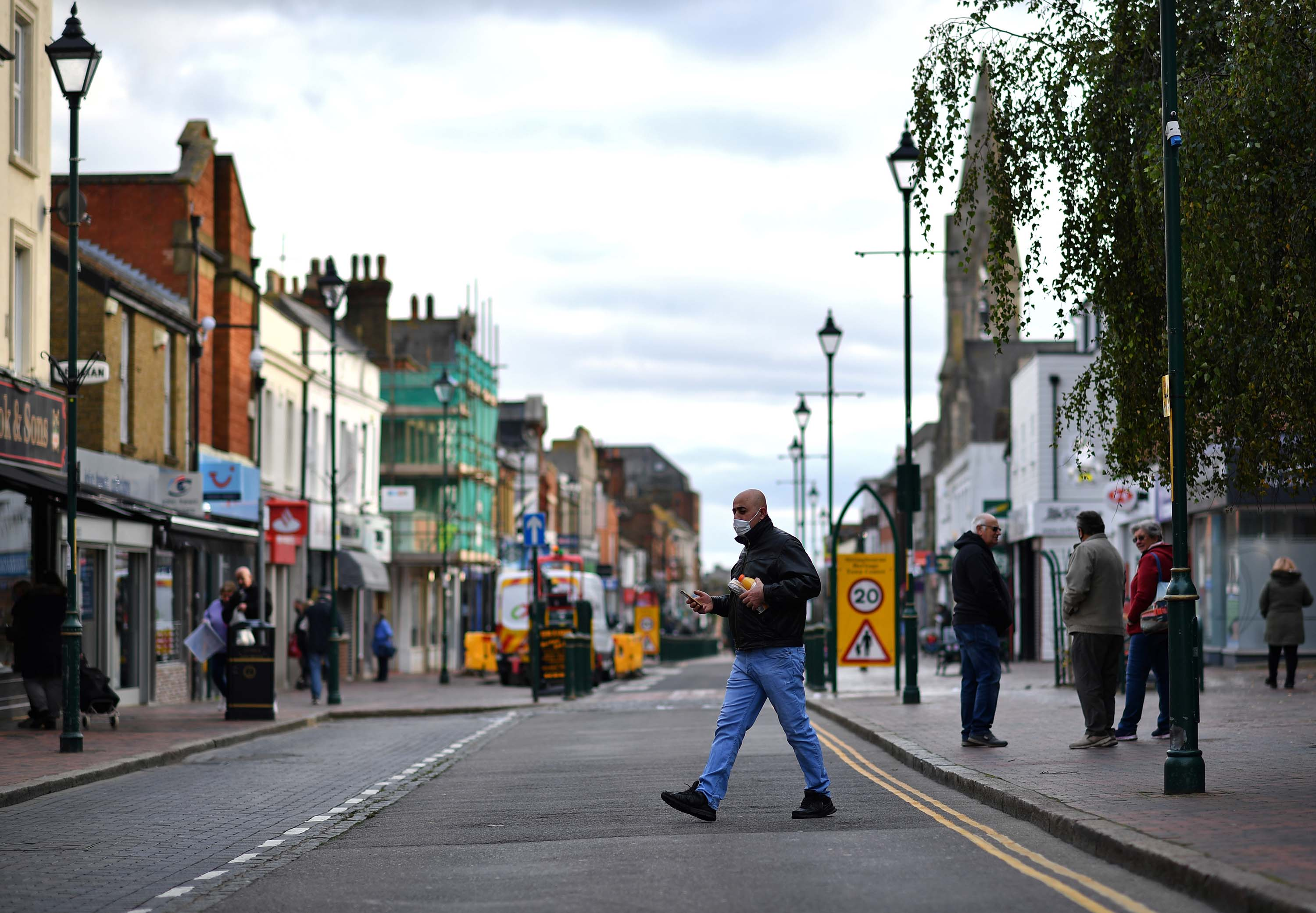 Pedestrians walk in a street in Sittingbourne, in the Swale district of Kent, England, which has become a coronavirus hotspot, on November 24.