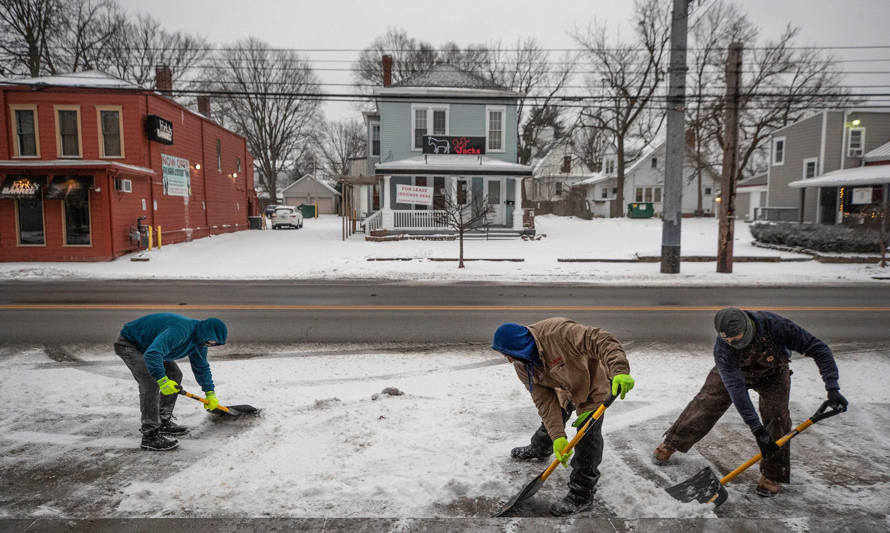 People shovel ice and snow from a winter storm in front of shops on Frankfort Avenue in Louisville, Kentucky, Monday February 15.
