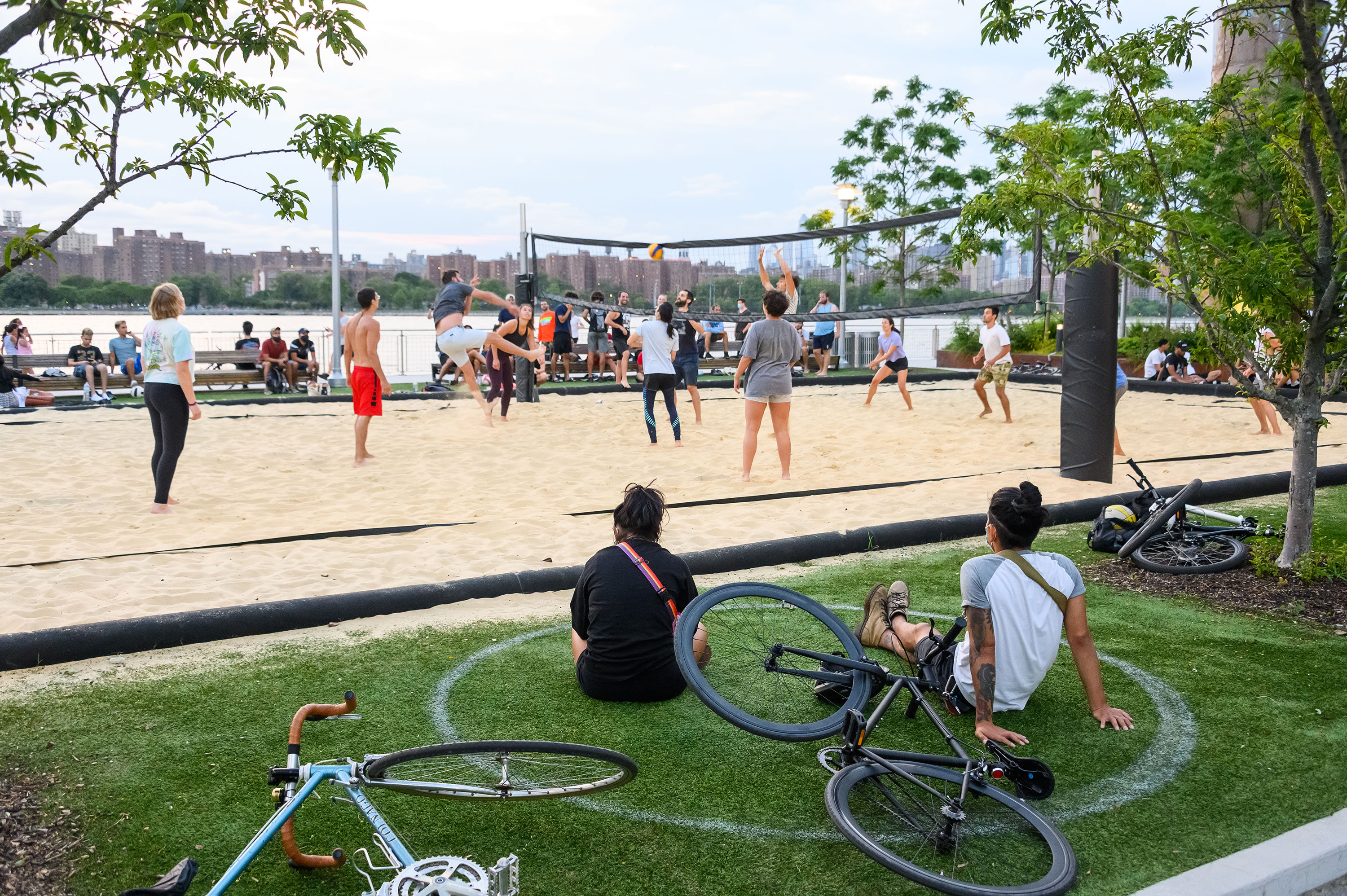People sit in a white circle and watch others play volleyball in Domino Park in the Williamsburg neighborhood of Brooklyn on July 16.