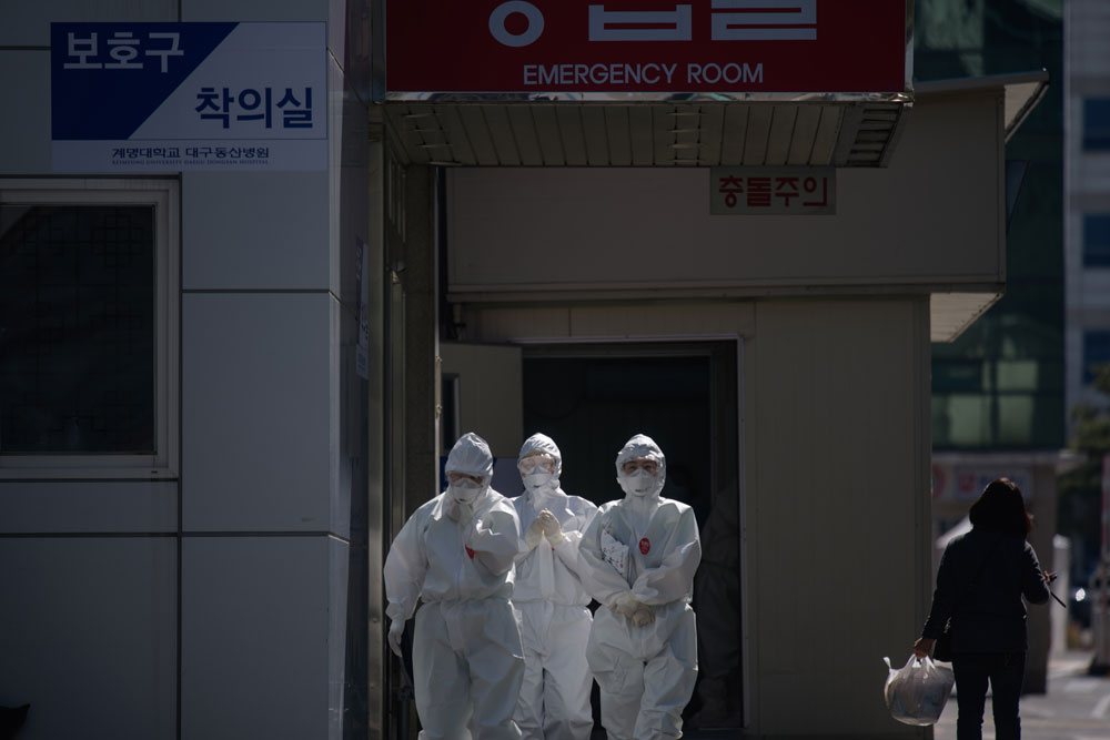 In this photo taken on March 12, medical workers wearing protective clothing against the coronavirus walk between buildings at the Keimyung University hospital in Daegu.
