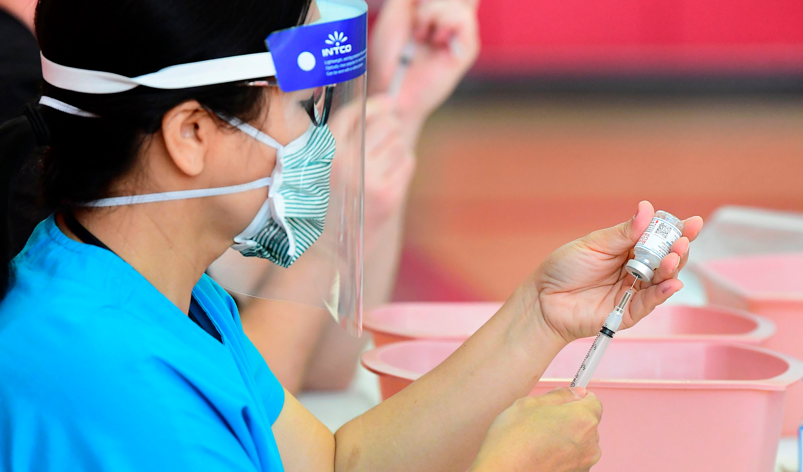 Registered nurses transfer the Moderna Covid-19 vaccine from a bottle into a syringe ready for vaccination at the Corona High School gymnasium in Corona, California on January 15