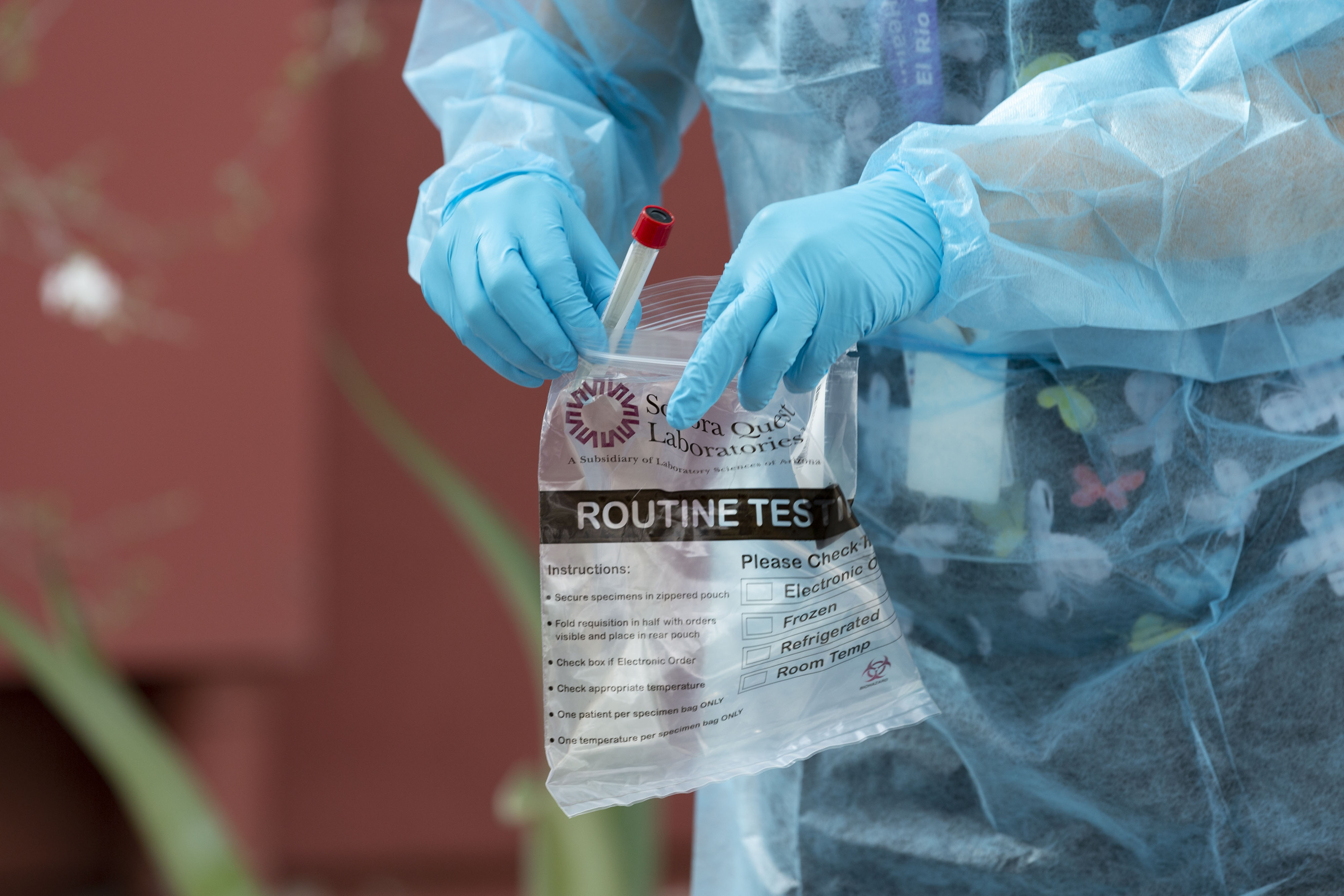 A health care worker bags a nasal swab at a Covid-19 testing site in Tucson, Arizona, on July 13.