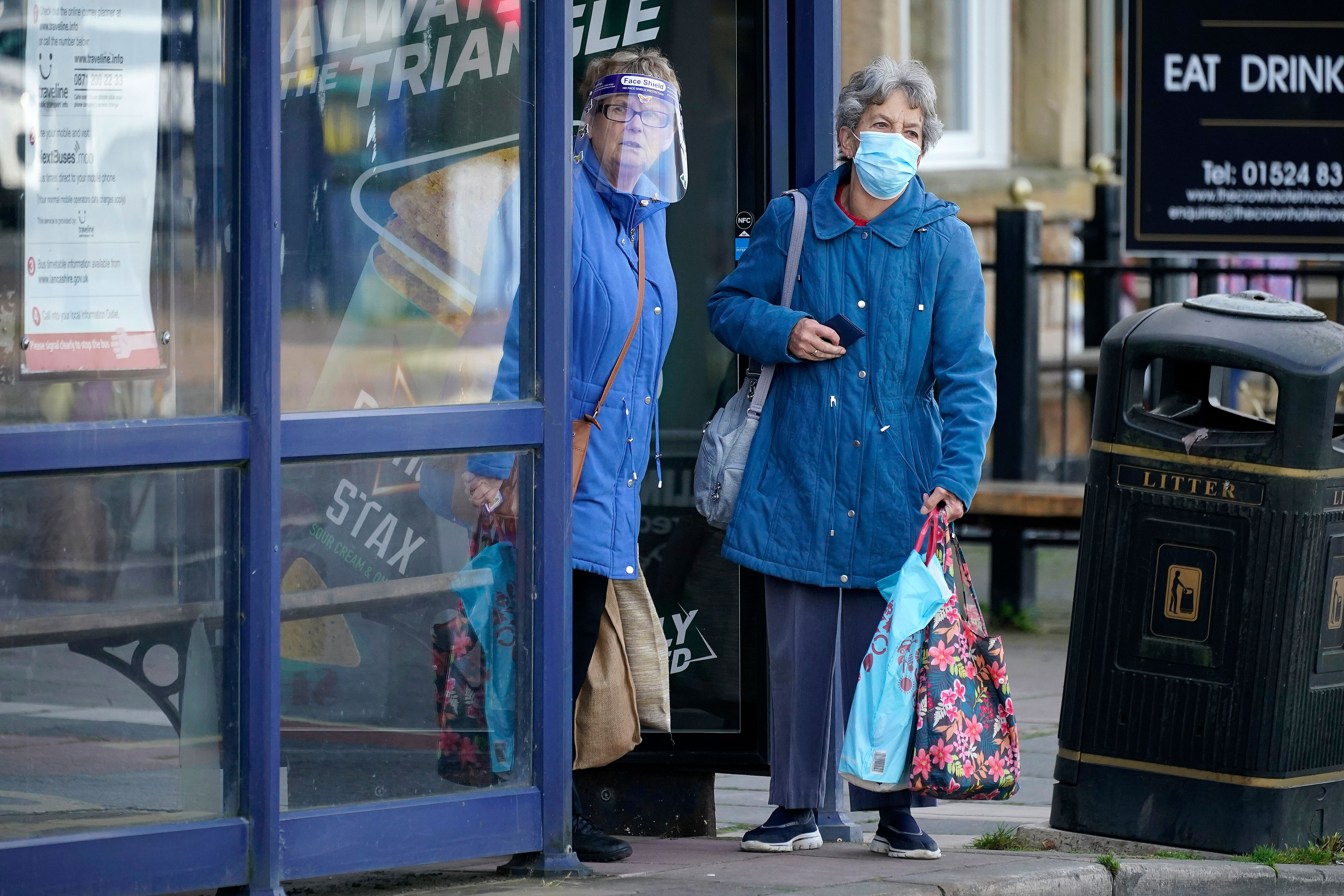 People in Morecambe, England, wait for a bus on October 16.