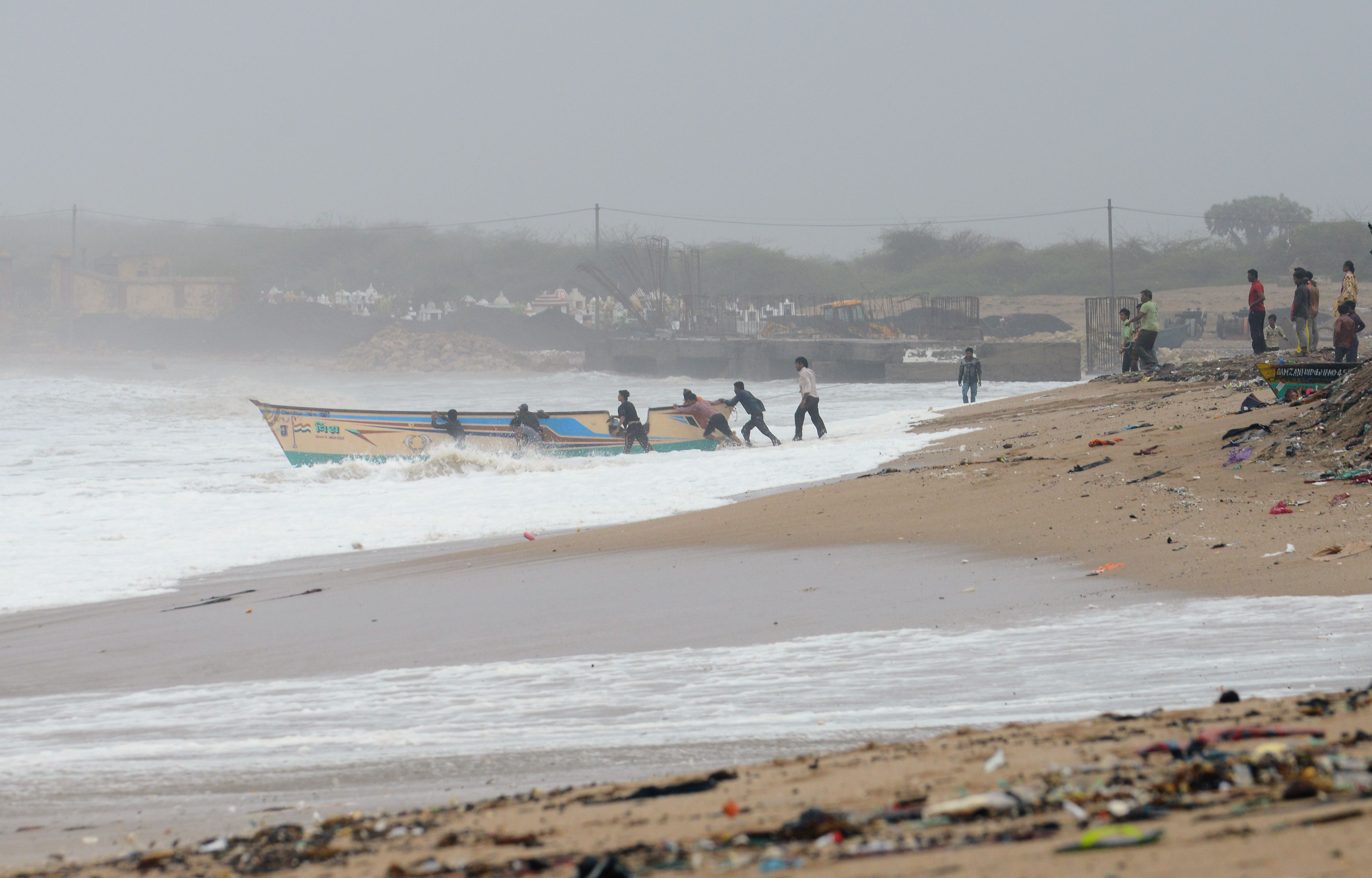 Indian fishermen try to save a boat from being washed out to sea on the outskirts of Veraval on June 13, 2019.