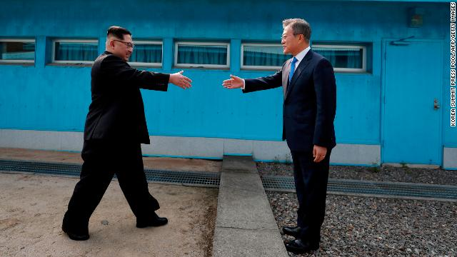 Kim shakes hands with Moon at the Military Demarcation Line that divides their countries ahead of their summit at the truce village of Panmunjom on April 27, 2018.