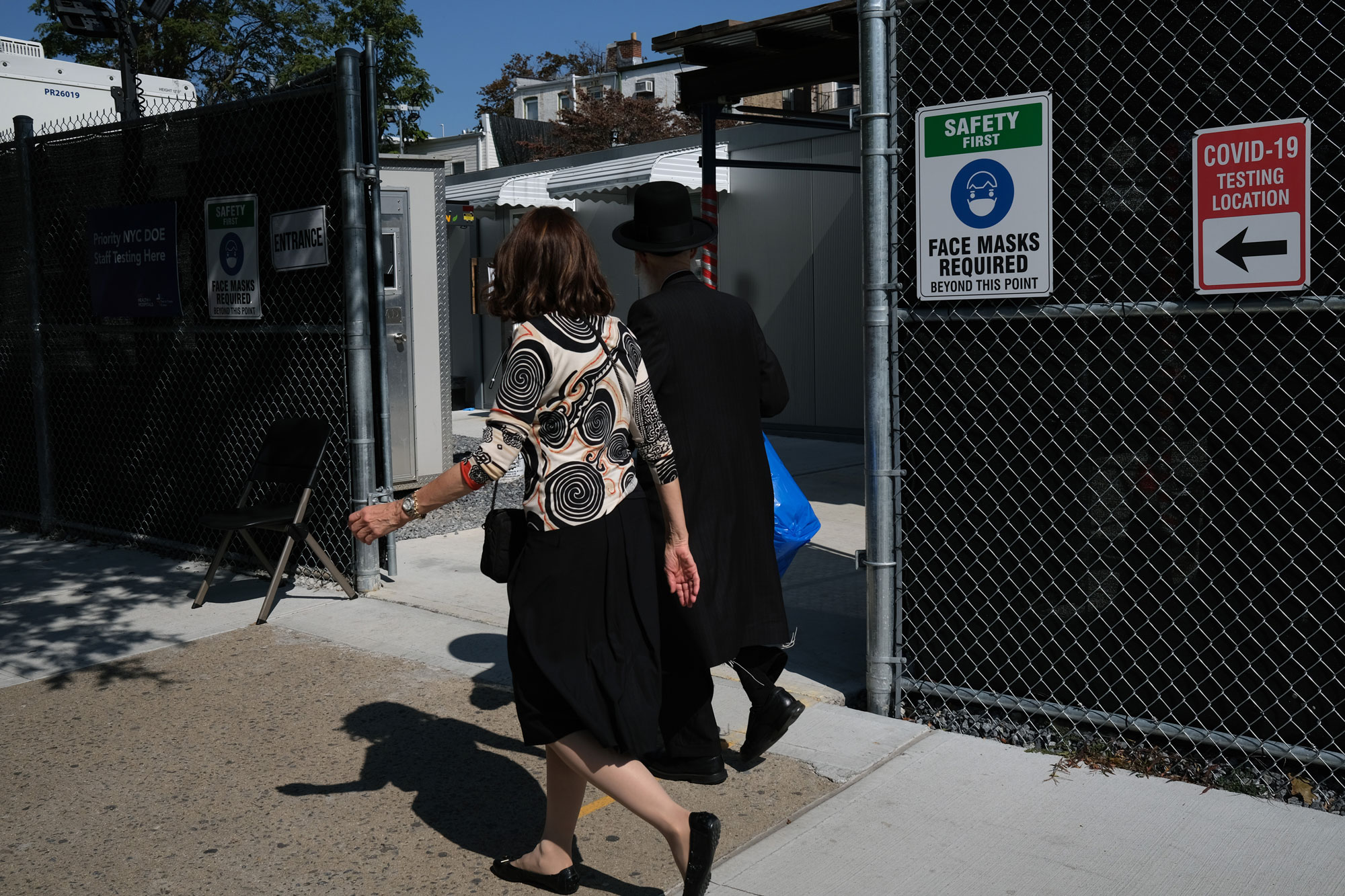 Residents walk by a COVID-19 testing site in the Brooklyn neighborhood of Borough Park on September 23 in New York City.