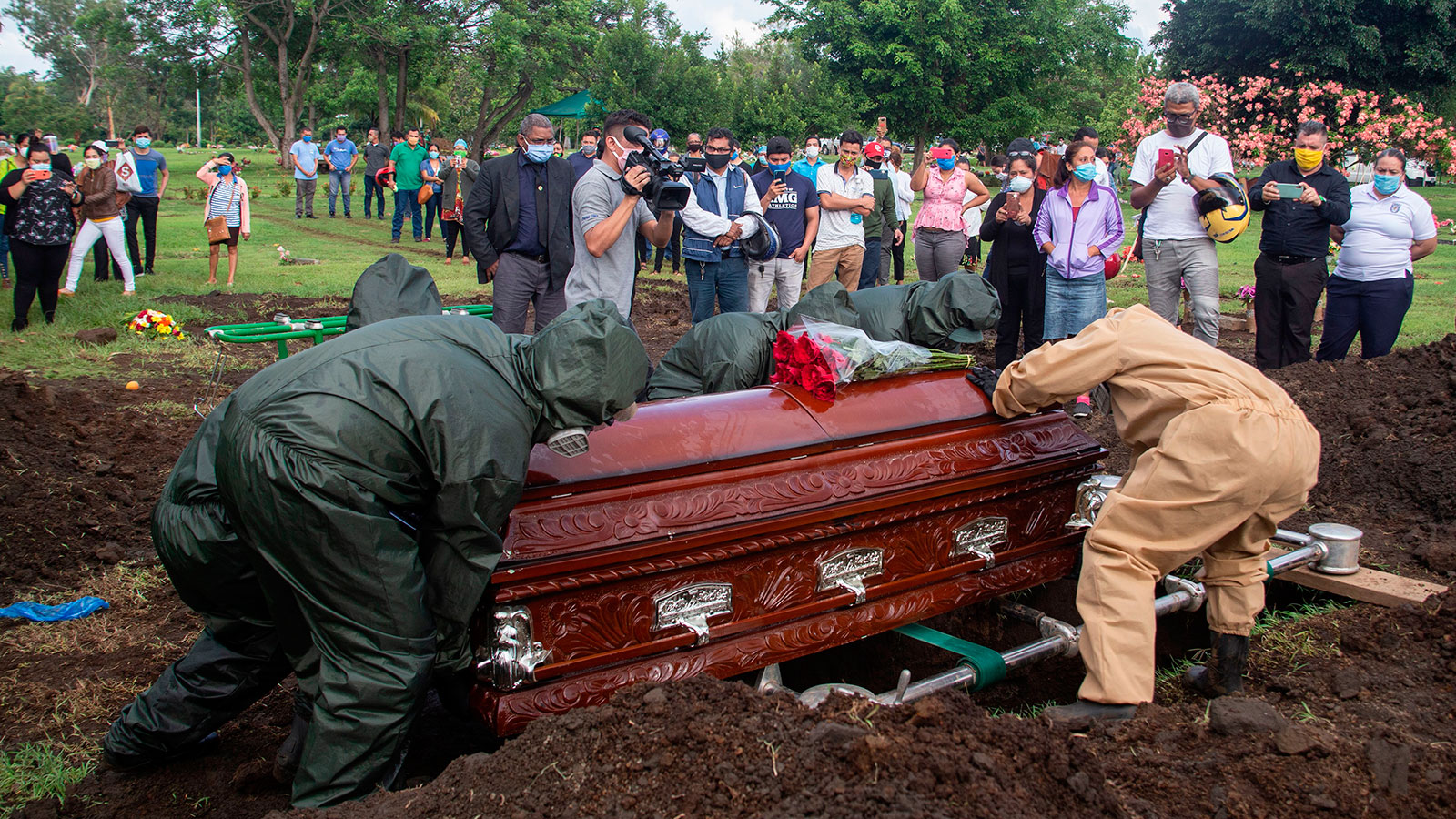 Gravediggers bury the coffin of a pastor, who allegedly died from Covid-19, during his funeral at the Jardines del Recuerdo Cemetery in Managua, Nicaragua on June 5.