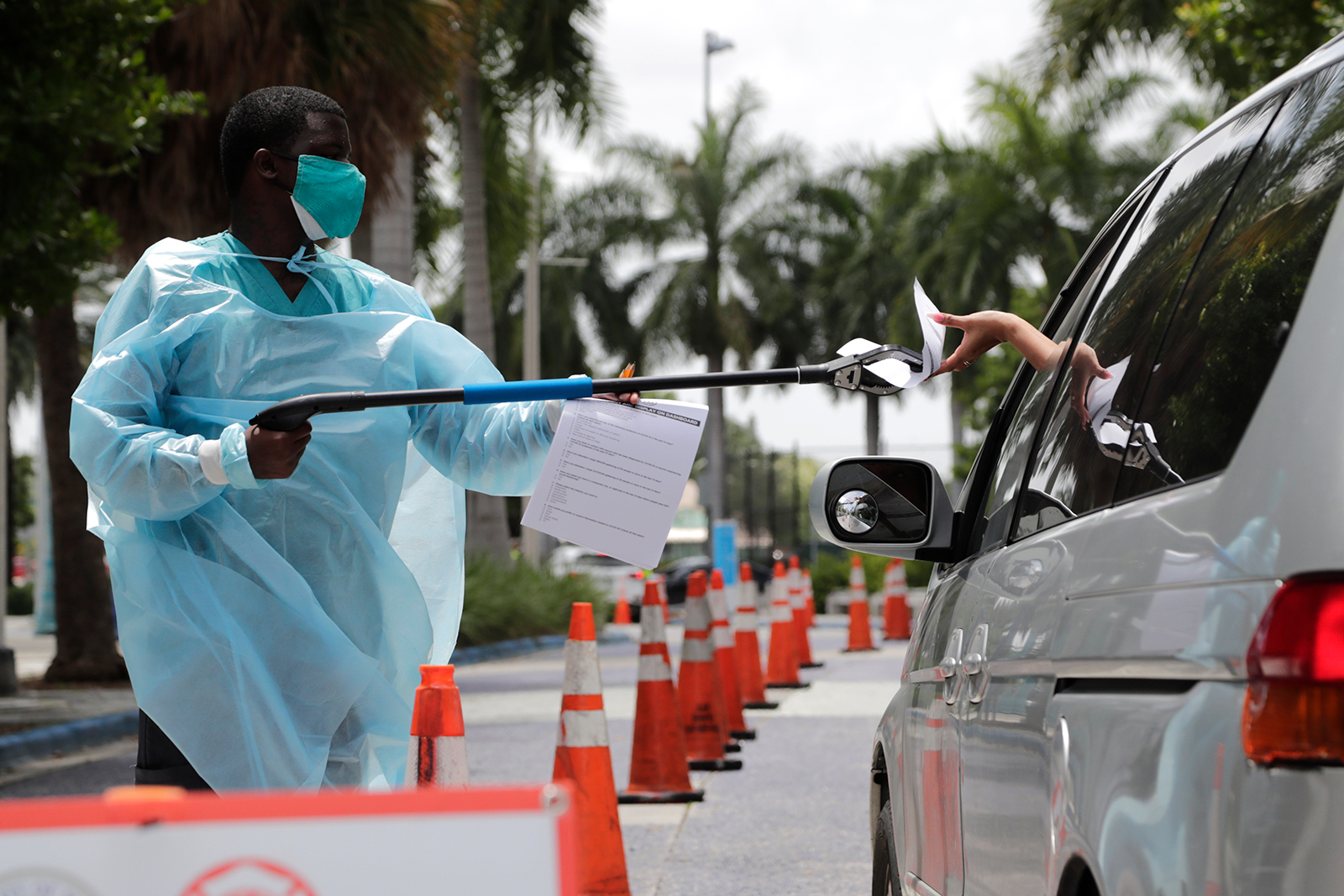 Healthcare worker Dante Hills, left, passes paperwork to a woman in a vehicle at a COVID-19 testing site outside of Marlins Park, Monday, July 27 in Miami.