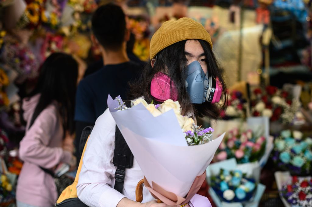 A man wearing a protective face mask as a preventative measure against the coronavirus buys flowers to mark Valentine's Day in Hong Kong on February 14.