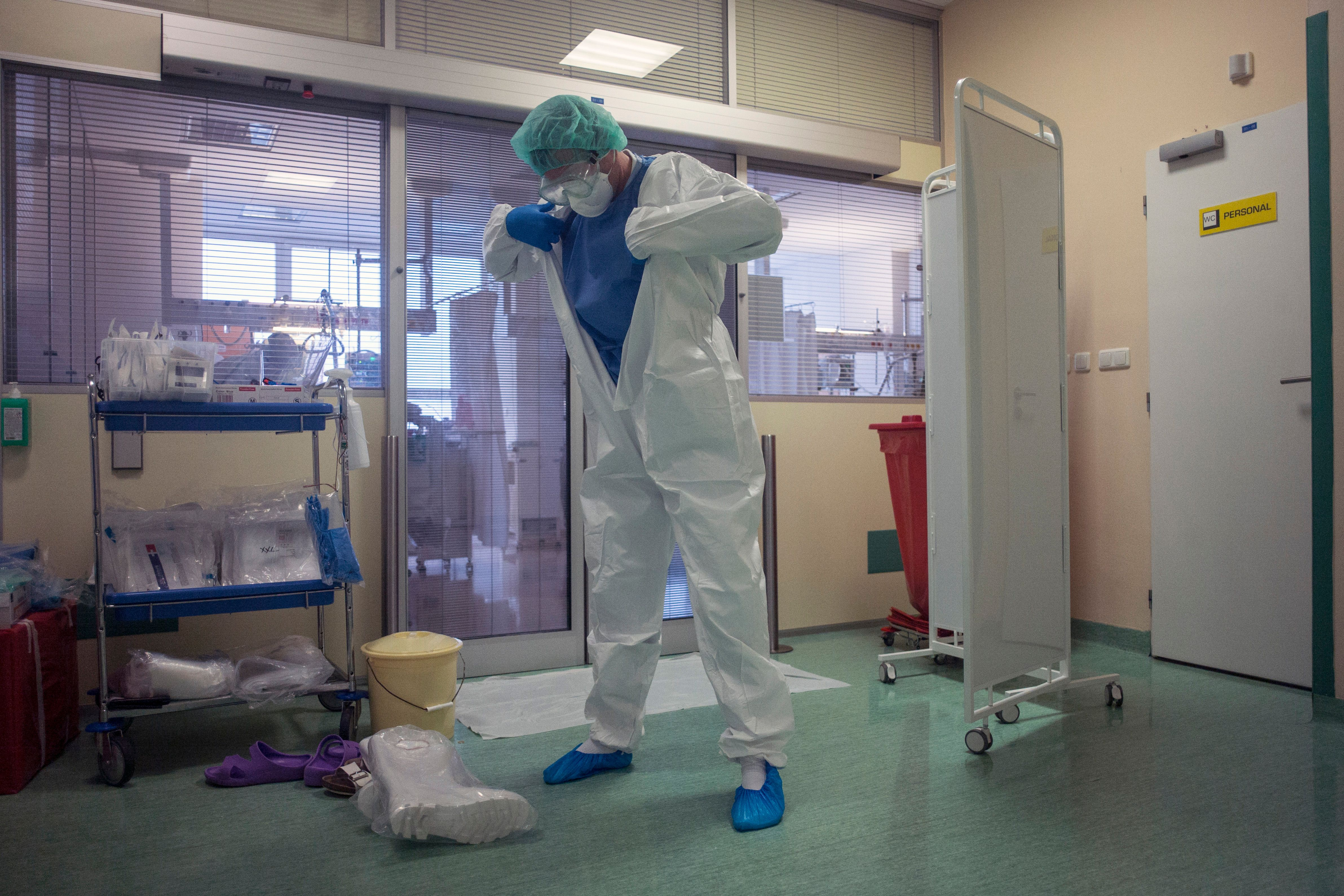 A healthcare worker puts on personal protective equipment (PPE) in front of the room for Covid-19 patients in an intensive care unit (ICU) at Thomayer hospital on October 14, in Prague.