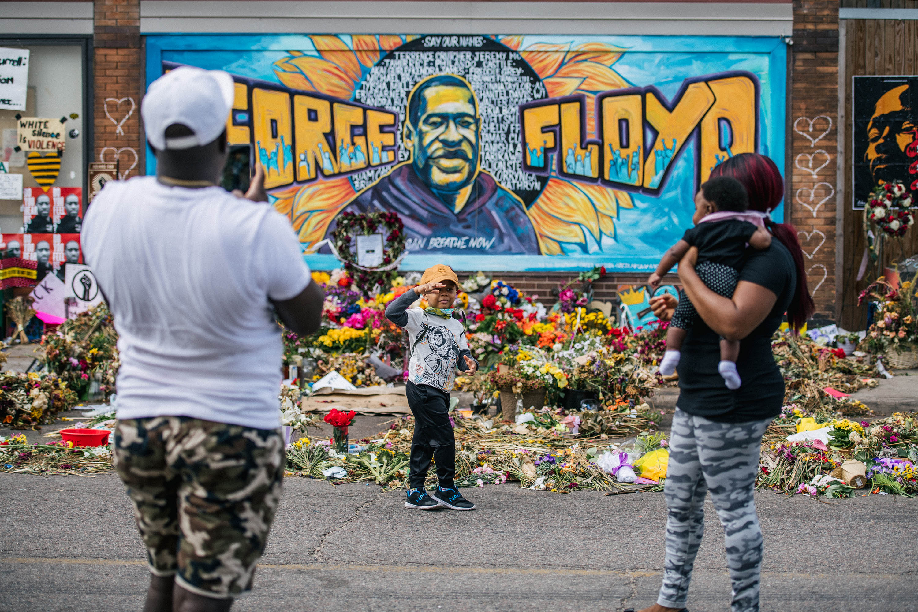 A family takes pictures in front of a mural of George Floyd on June 10, in Minneapolis, Minnesota.