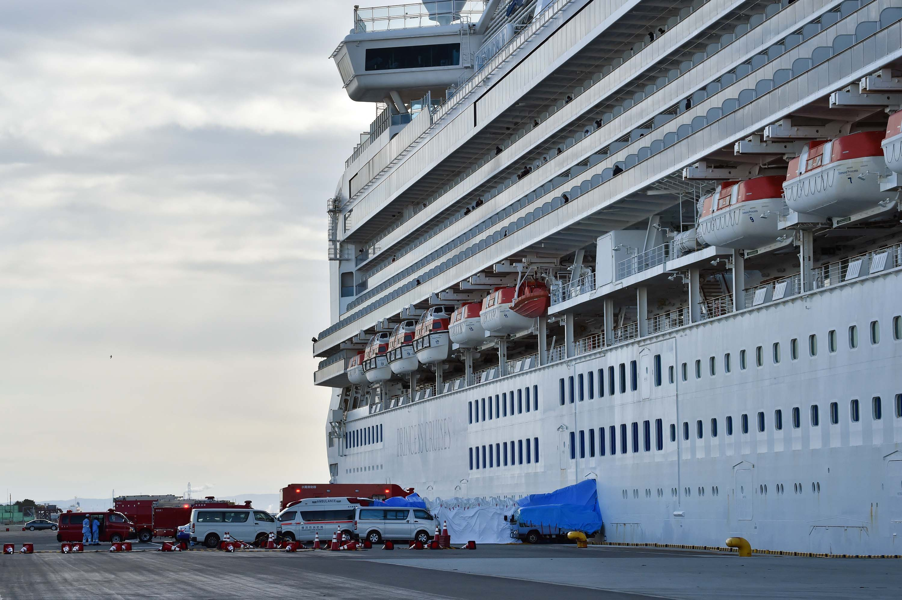 An ambulance waits for patients who tested positive for the coronavirus aboard the Diamond Princess cruise ship, docked at the Daikoku Pier Cruise Terminal in Yokohama, Japan on Thursday.