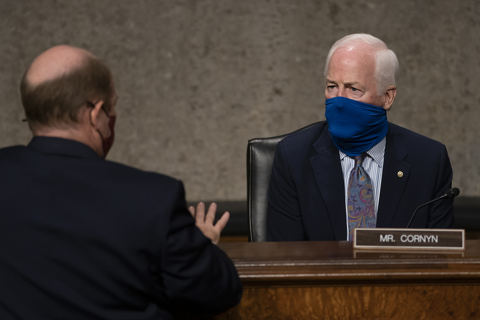 "Sen. John Cornyn talks with Sen. Chris Coons before a Senate Judiciary Committee hearing on ""Oversight of the Crossfire Hurricane Investigation"" on Capitol Hill on August 5 in Washington."