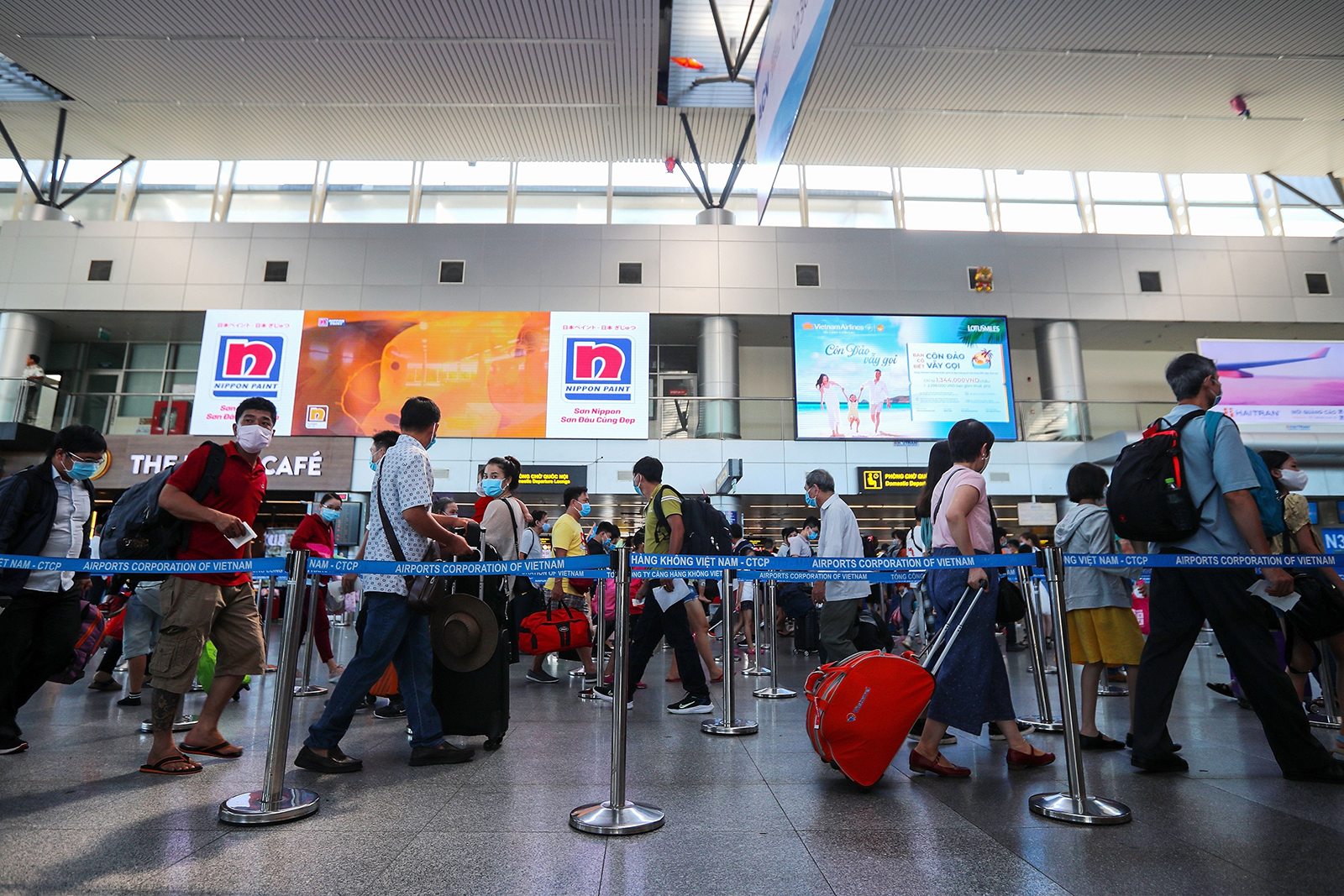 Passengers wearing face masks queue up for check-in at the departures terminal of Da Nang International Airport in Vietnam on July 27.