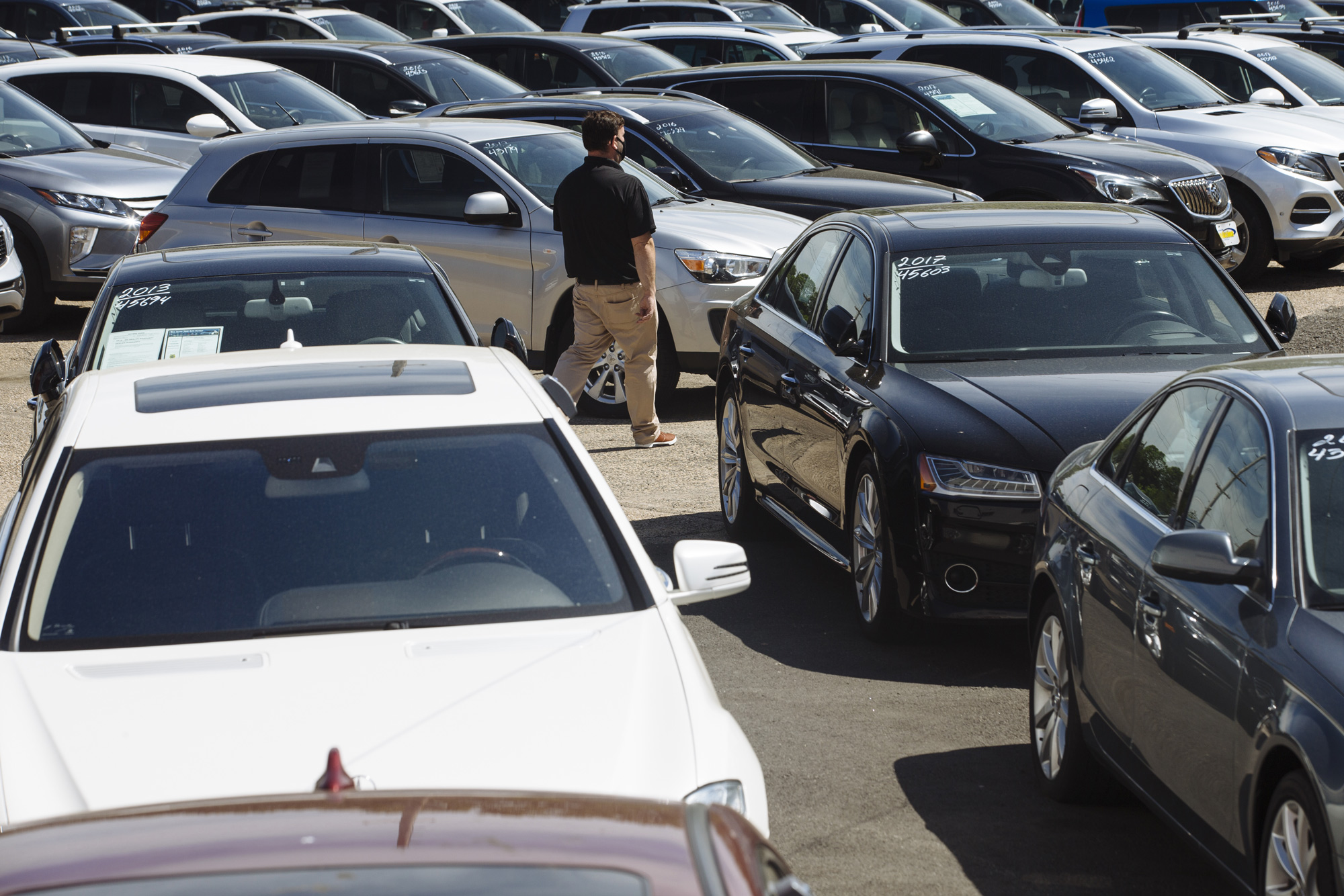 A car dealer walks past cars for sale at a used car dealership in Jersey City, New Jersey, on May 20.