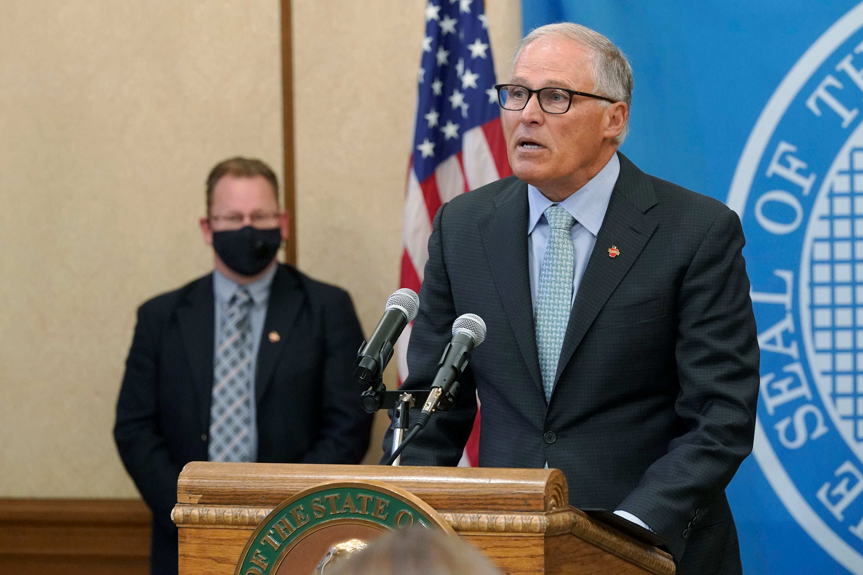Washington Gov. Jay Inslee, right, speaks at a news conference on August 18 at the Capitol in Olympia, Washington.