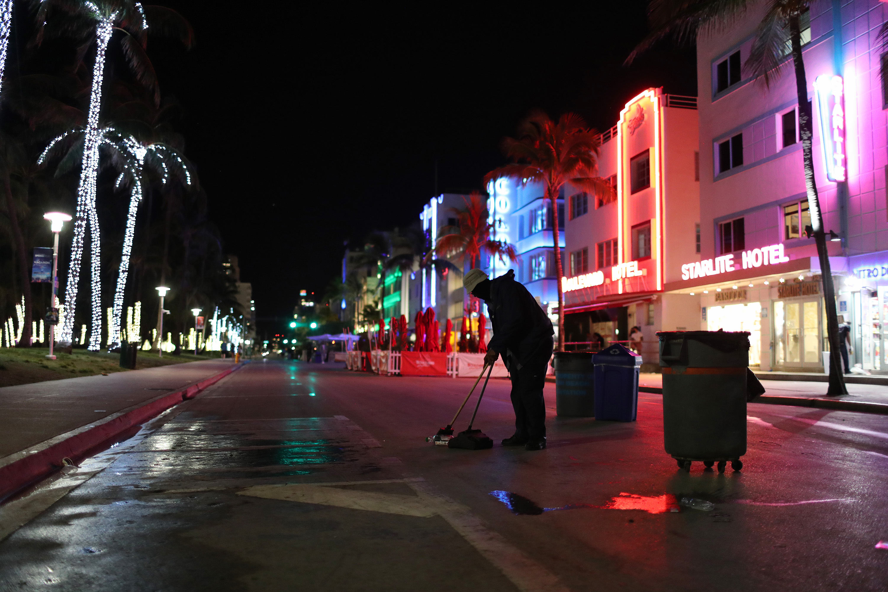 A City employee cleans up on Ocean Drive after people left due to an 8 p.m. curfew on March 21 in Miami Beach, Florida.