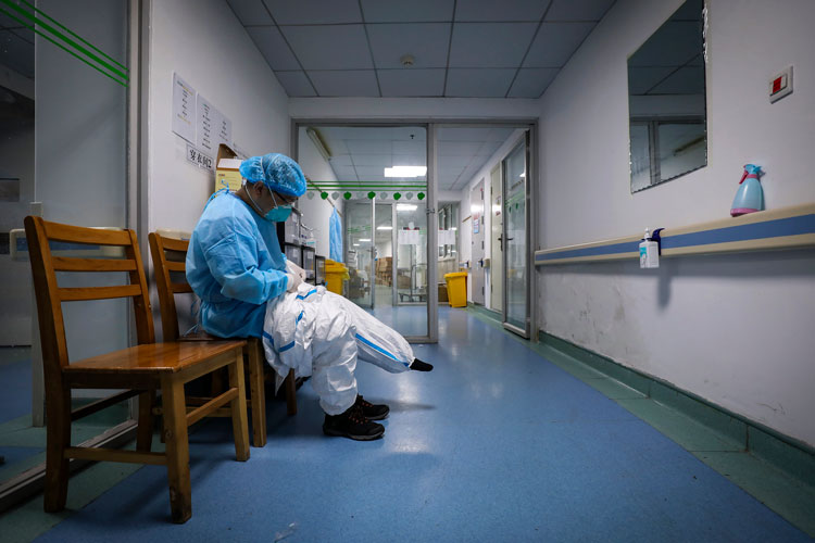 A doctor puts on a protective suit as he prepares to check on patients at Jinyintan Hospital designated for coronavirus patients, in Wuhan in central China's Hubei province on Sunday, February 16.