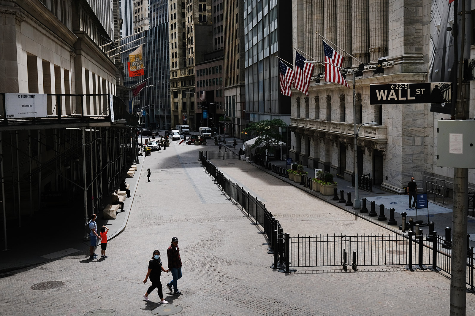 People walk by the New York Stock Exchange on June 15.