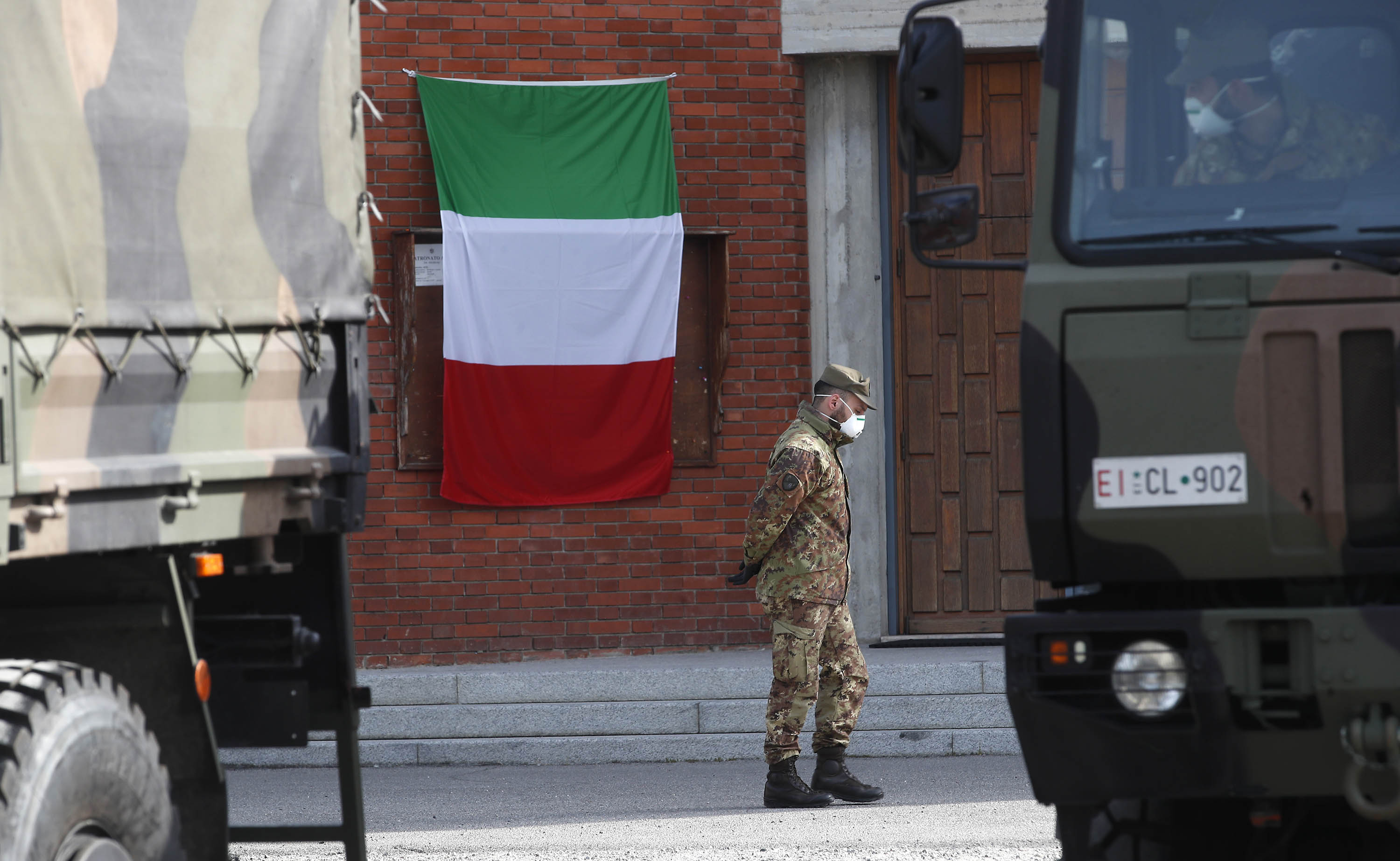An Italian flag hangs outside the San Giuseppe church in Seriate, Italy, as a soldier waits to load coffins to be taken to crematoriums, on March 28.