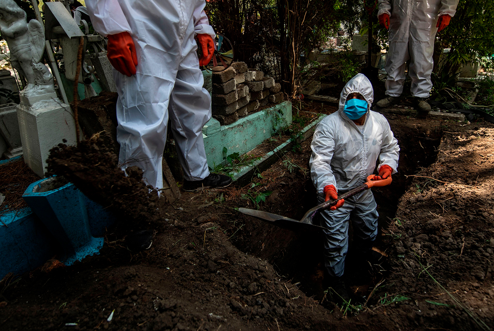 A gravedigger works during a funeral at the San Isidro cemetery in Azcapotzalco, in Mexico City, on August 6.