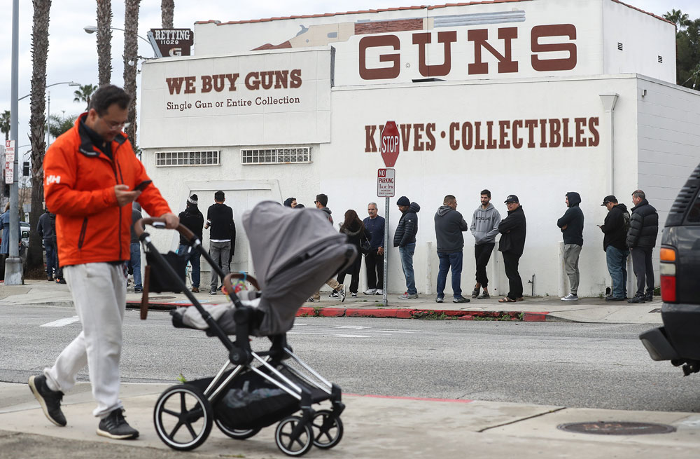 A man walks with a stroller as people stand in line outside the Martin B. Retting gun store on March 15, in Culver City, California.