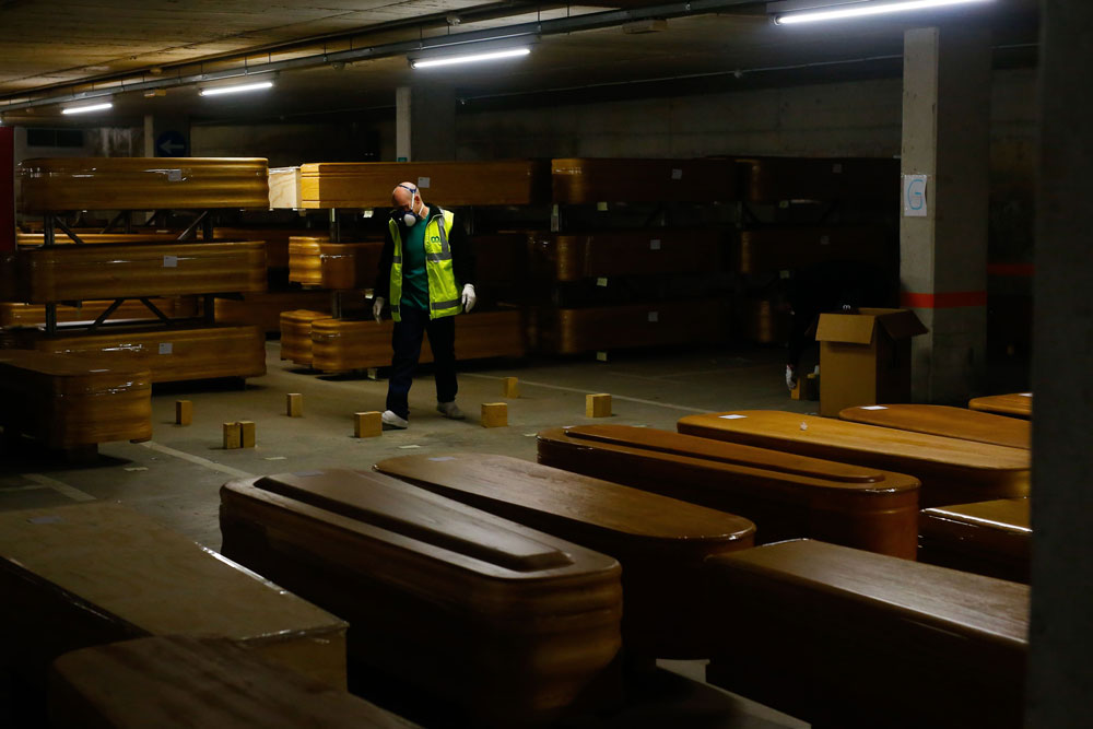 A mortuary worker prepares supports for coffins, most of them containing Covid-19 victims, at Collserola funeral home near Barcelona, Spain.