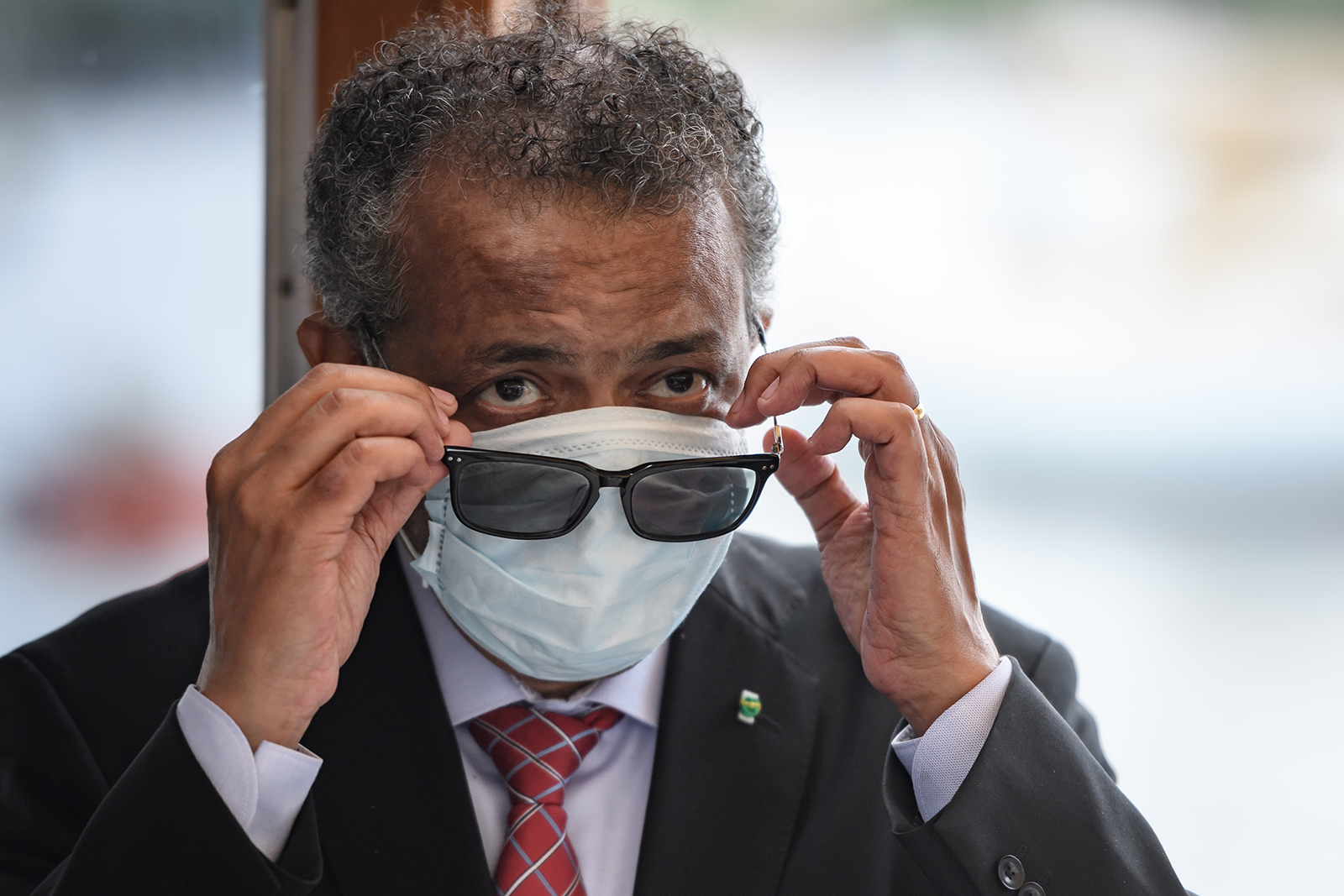 """World Health Organization Director-General Tedros Adhanom Ghebreyesus wears a mask after leaving a ceremony of the restarting of Geneva's landmark fountain, known as """"Jet d'Eau"""" on Thursday, June 11, in Geneva."""