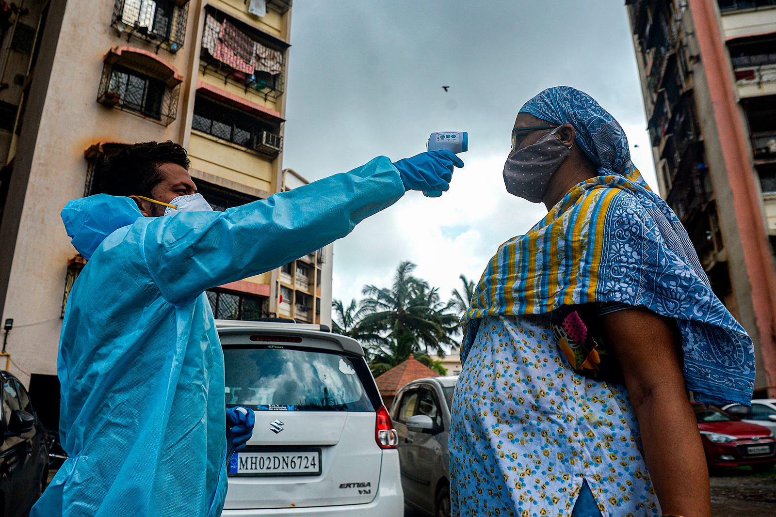 A health worker, left, takes the temperature of a resident during a door-to-door medical screening drive in Mumbai on Monday, July 20.