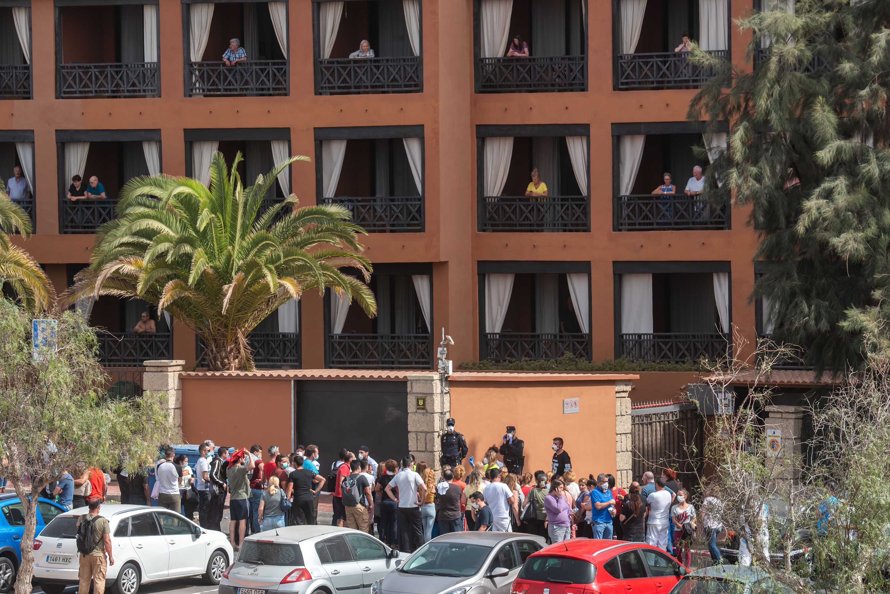 A psychologist talks to a group of workers on Tuesday outside the H10 Costa Adeje Palace Hotel in Tenerife, Spain, where hundreds of people were confined after an Italian tourist was hospitalised with a suspected case of coronavirus.